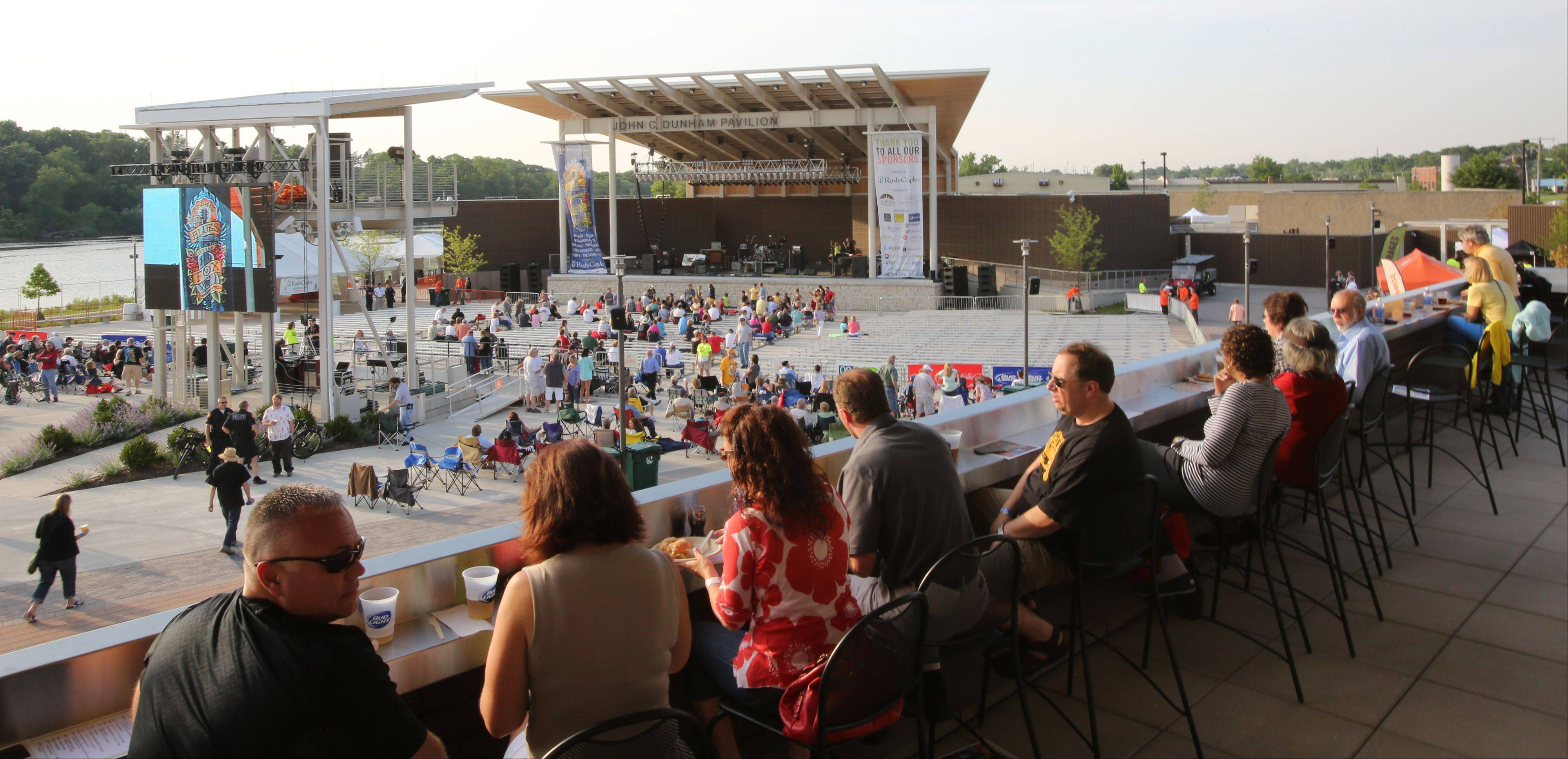 Festival goers on the VIP deck watch the crowd fill in during the opening night of RiverEdge Park, coinciding with the 17th annual Blues on the Fox festival.