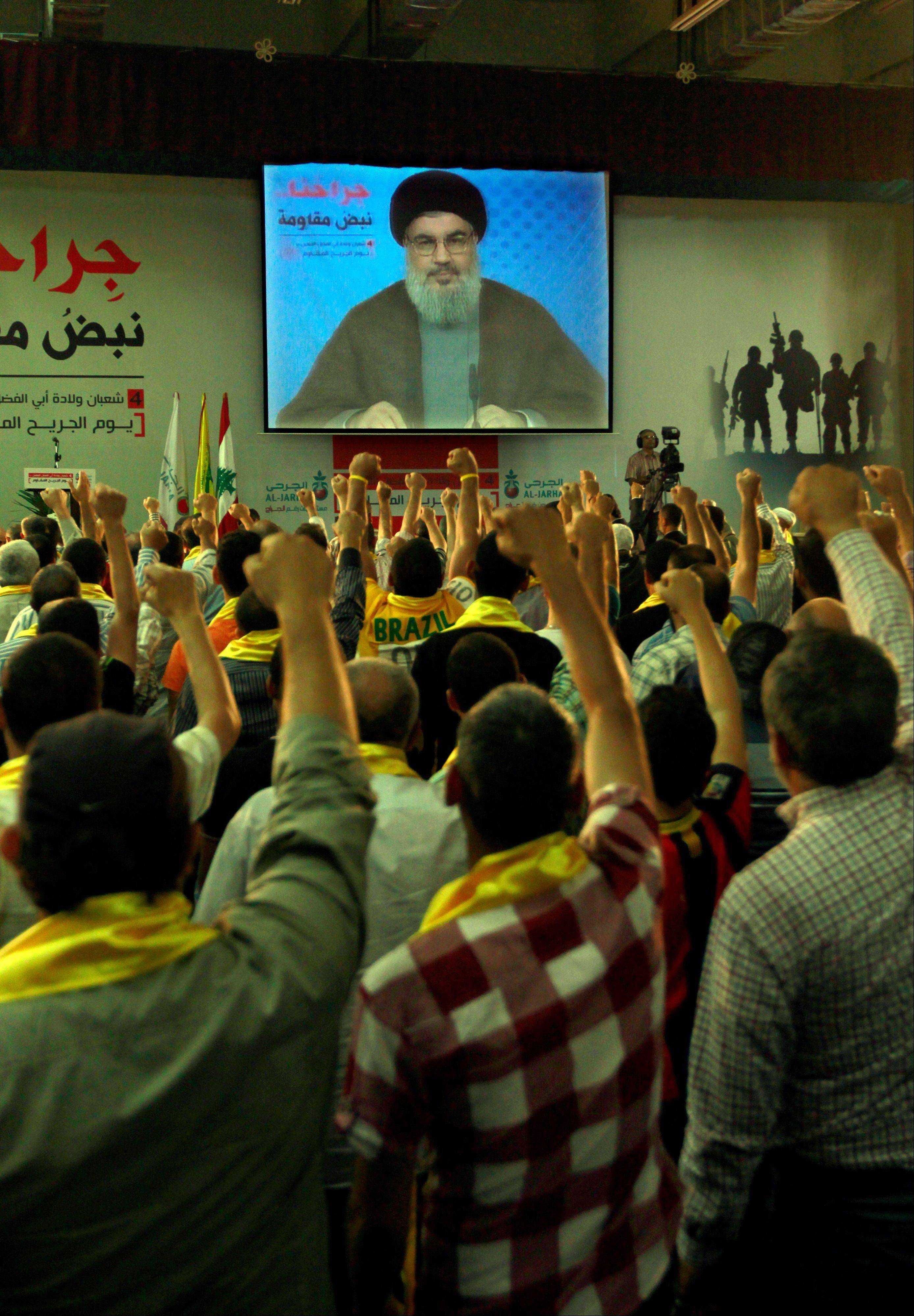 Hezbollah supporters raise their hands in salute as Hezbollah leader Sheik Hassan Nasrallah speaks on a screen Friday via a video link from a secret place, in the southern suburb of Beirut, Lebanon. Nasal said his group will continue to fight in Syria.
