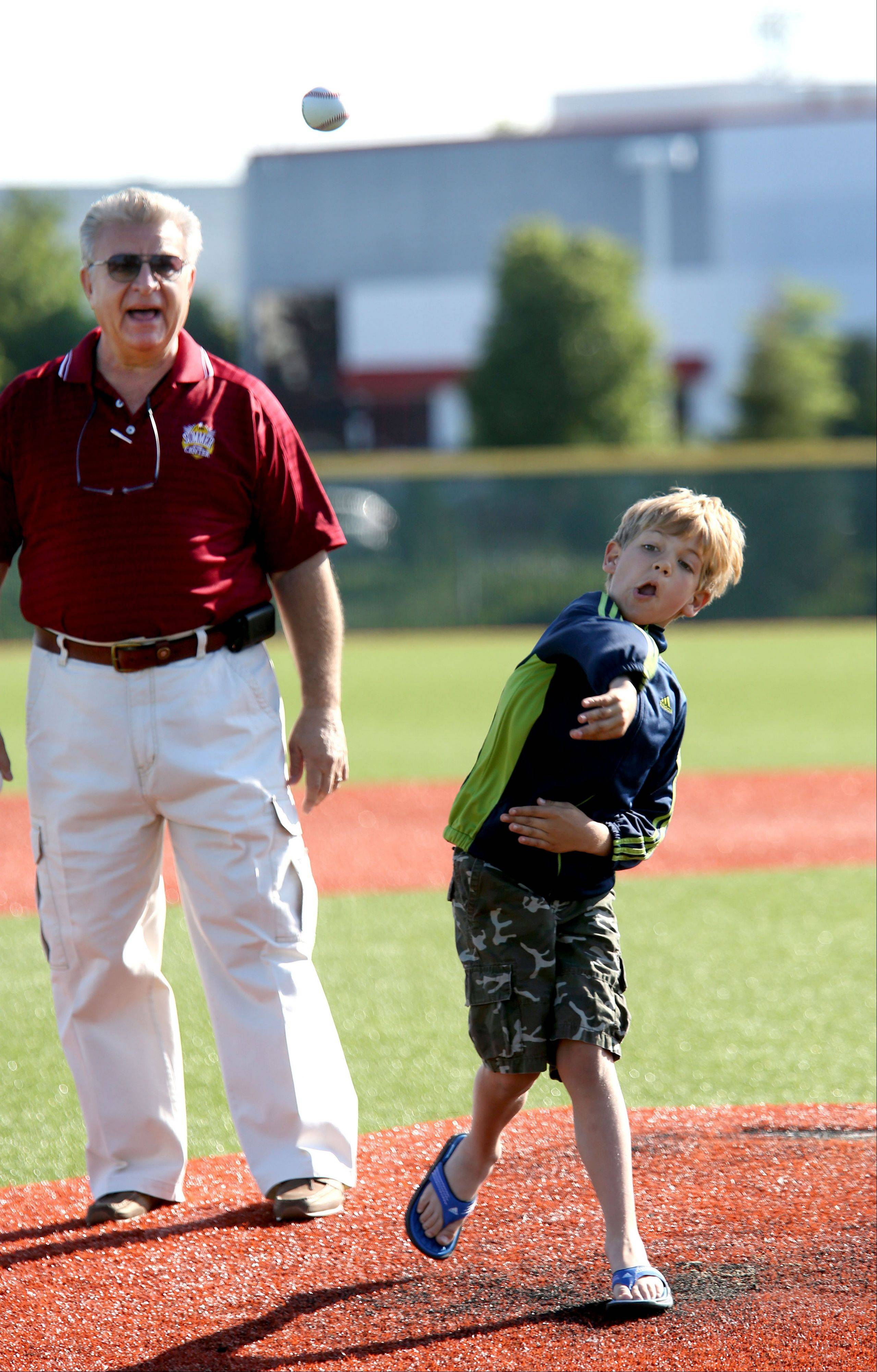 Carol Stream Village President Frank Saverino cheers on his 7-year-old grandson, Dominic, as he throws out one of the ceremonial first pitches Friday at the opening of the American Legion Post 76 Summer Classic Tournament.