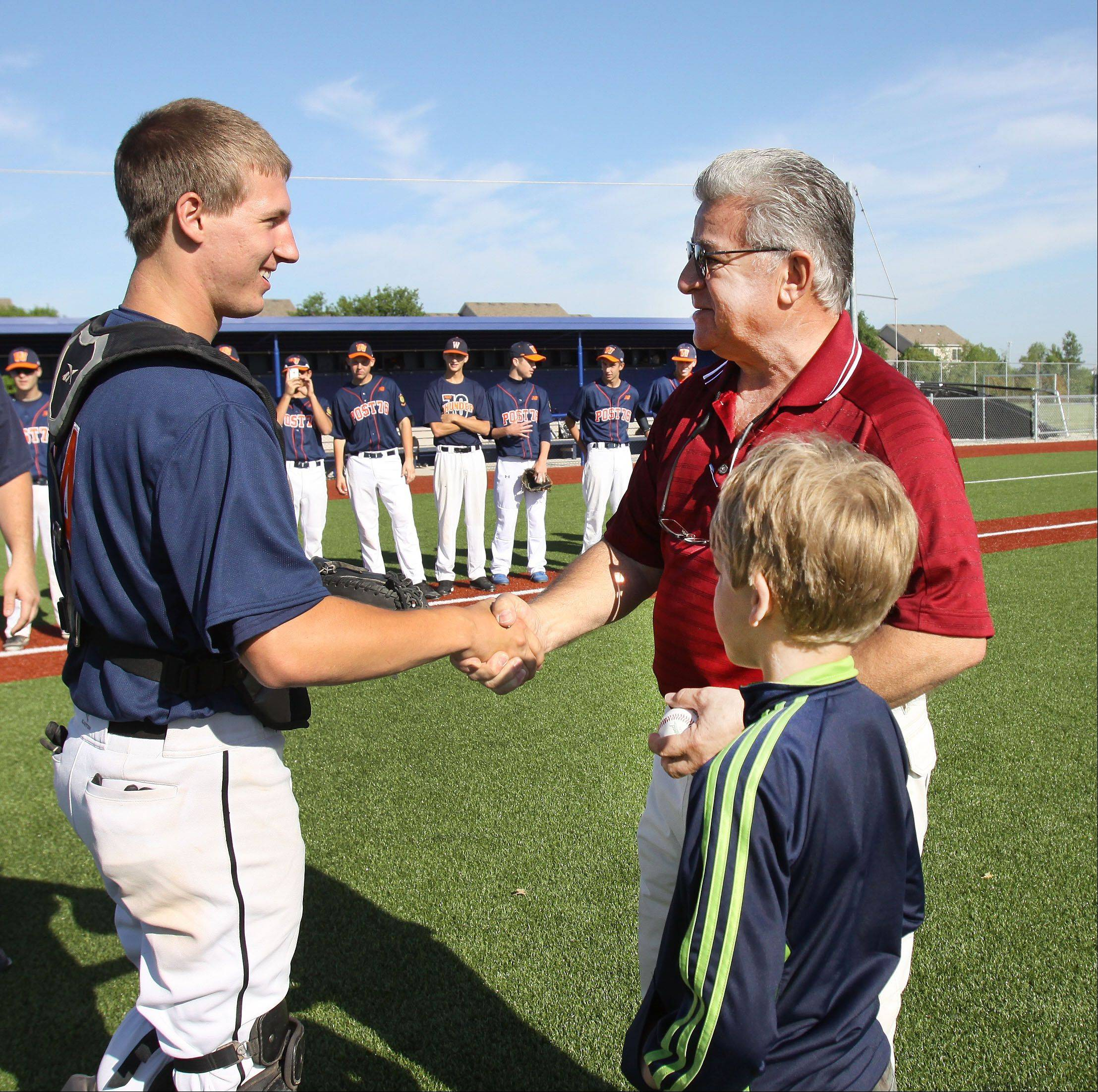 Carol Stream Village President Frank Saverino and his 7-year-old grandson, Dominic, talk with American Legion Post 76 baseball team catcher Jeff LaPage of Glenbard North Friday after throwing ceremonial first pitches at the opening of the post's Summer Classic Tournament.