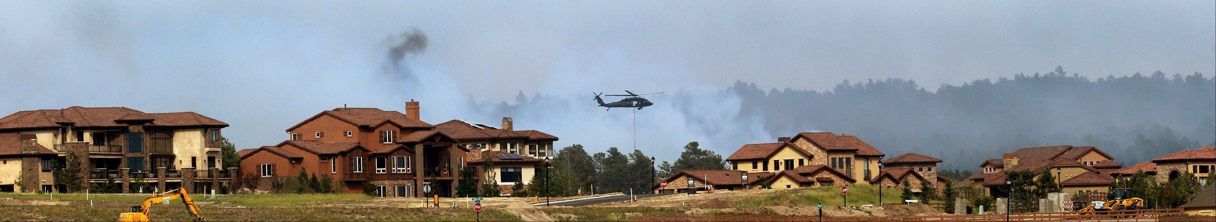 An Army helicopter drops water Thursday on the Black Forest wildfire behind houses on the Flying Horse Ranch in Colorado Springs, Colo.