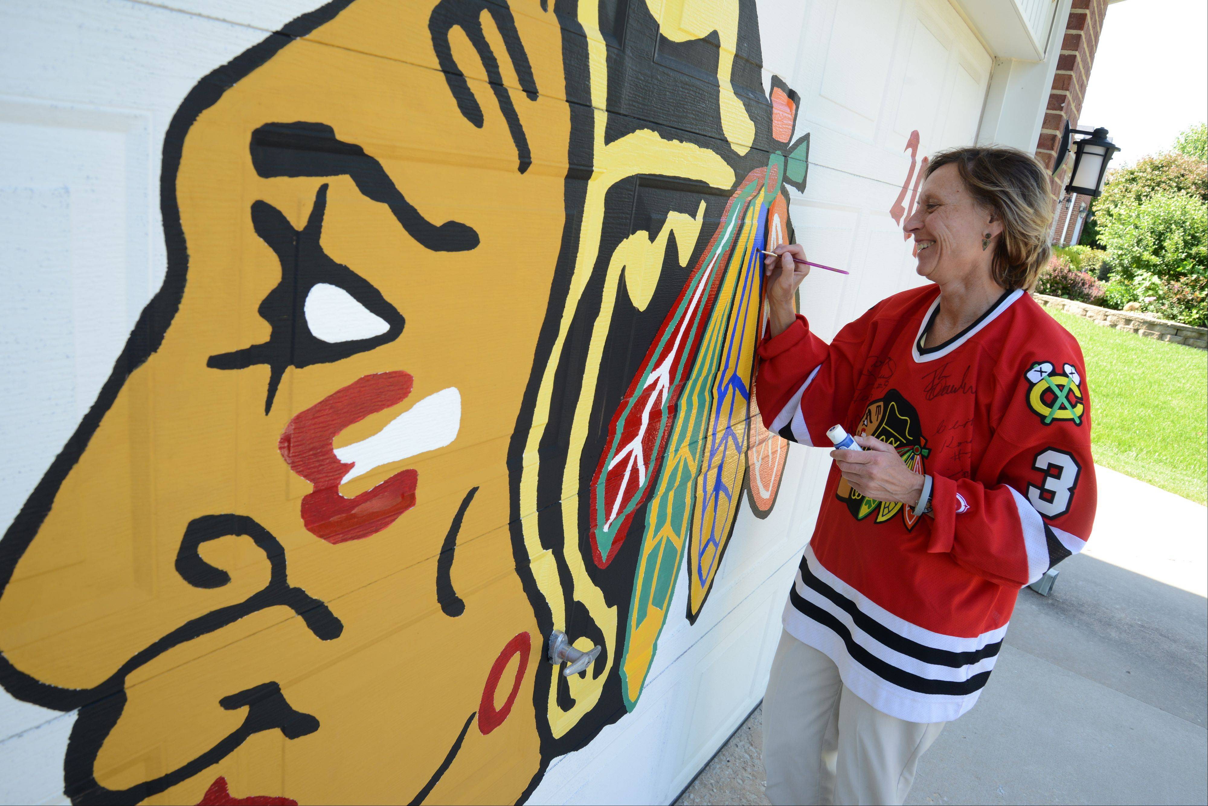 Hawks Lee Ann Stawczyk of Woodridge touches up her hand-painted Hawks logo, one of several ways she's demonstrated her fanaticism about the Hawks.