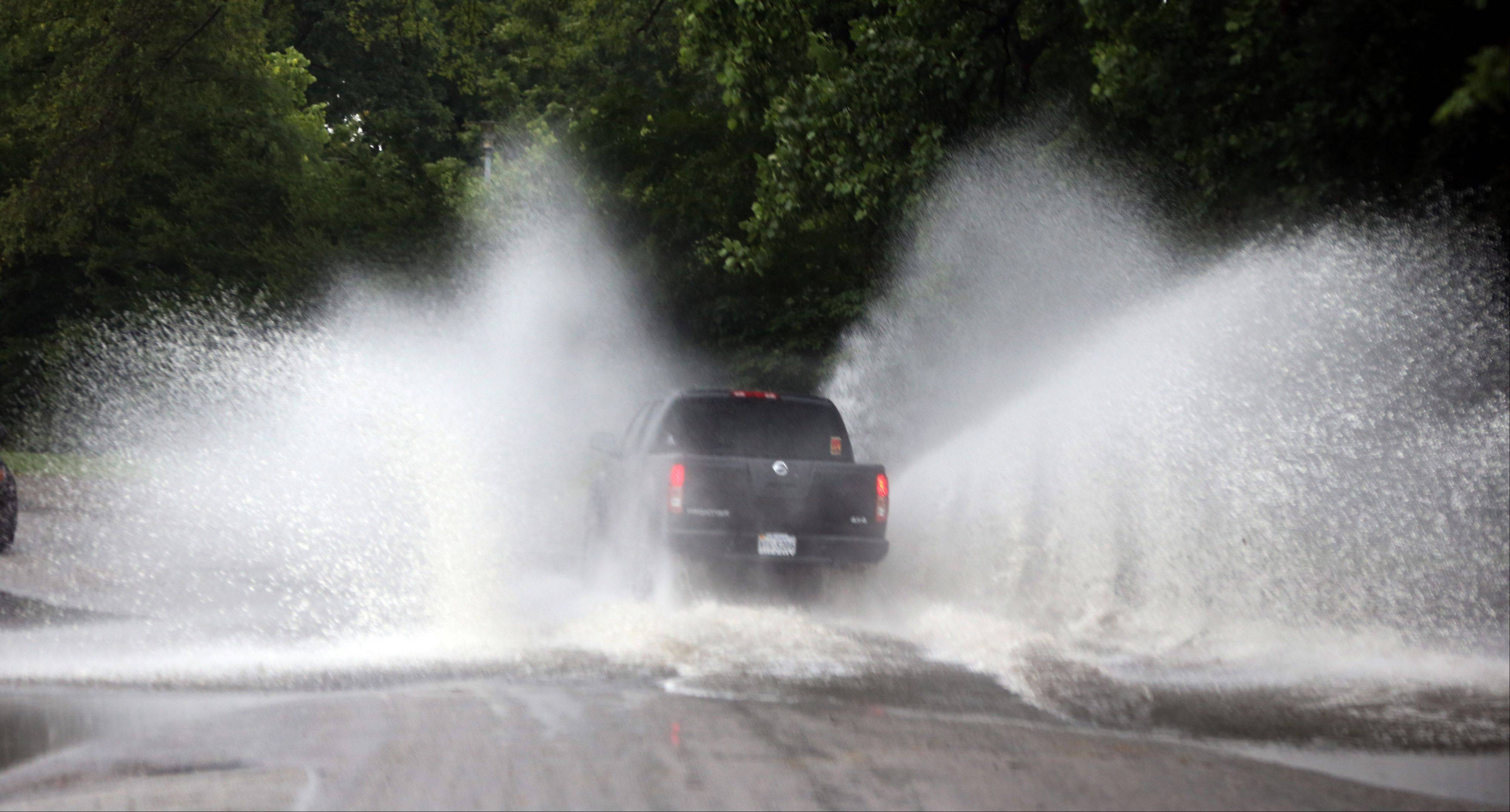 A pickup truck creates a huge splash as it drives through water on the road around Shield's Lake near the Maymont Nature Center in Richmond, Va., Thursday, June 13, 2013 after a strong line of storms moved through the area.