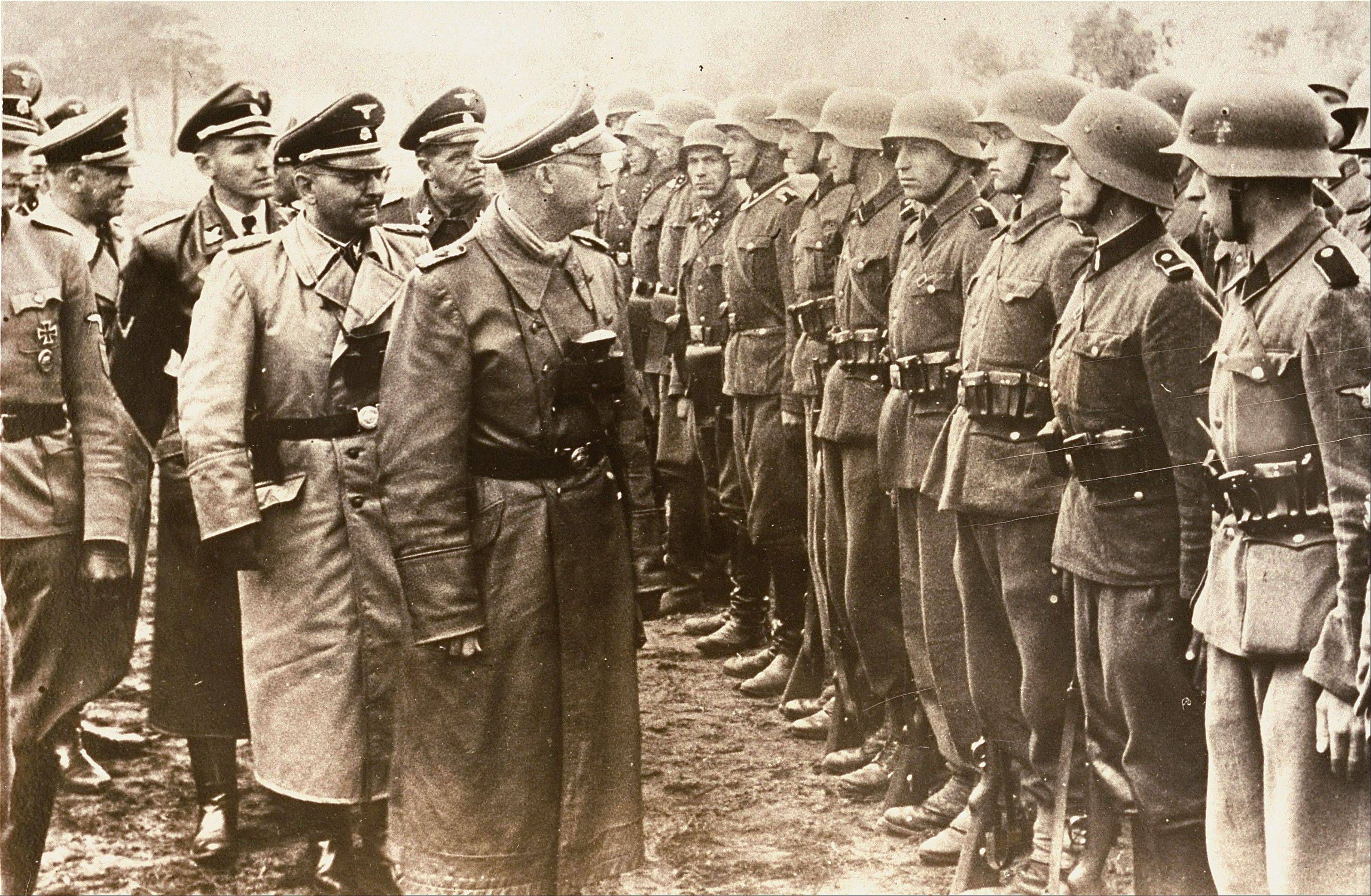 This June 3, 1944 photo provided by the US Holocaust Memorial Museum shows Heinrich Himmler, center, SS Reichsfuehrer-SS, head of the Gestapo and the Waffen-SS, and Minister of the Interior of Nazi Germany from 1943 to 1945, as he reviews troops of the Galician SS-Volunteer Infantry Division Michael Karkoc a top commander whose Nazi SS-led unit is blamed for burning villages filled with women and children lied to American immigration officials to get into the United States and has been living in Minnesota since shortly after World War II.