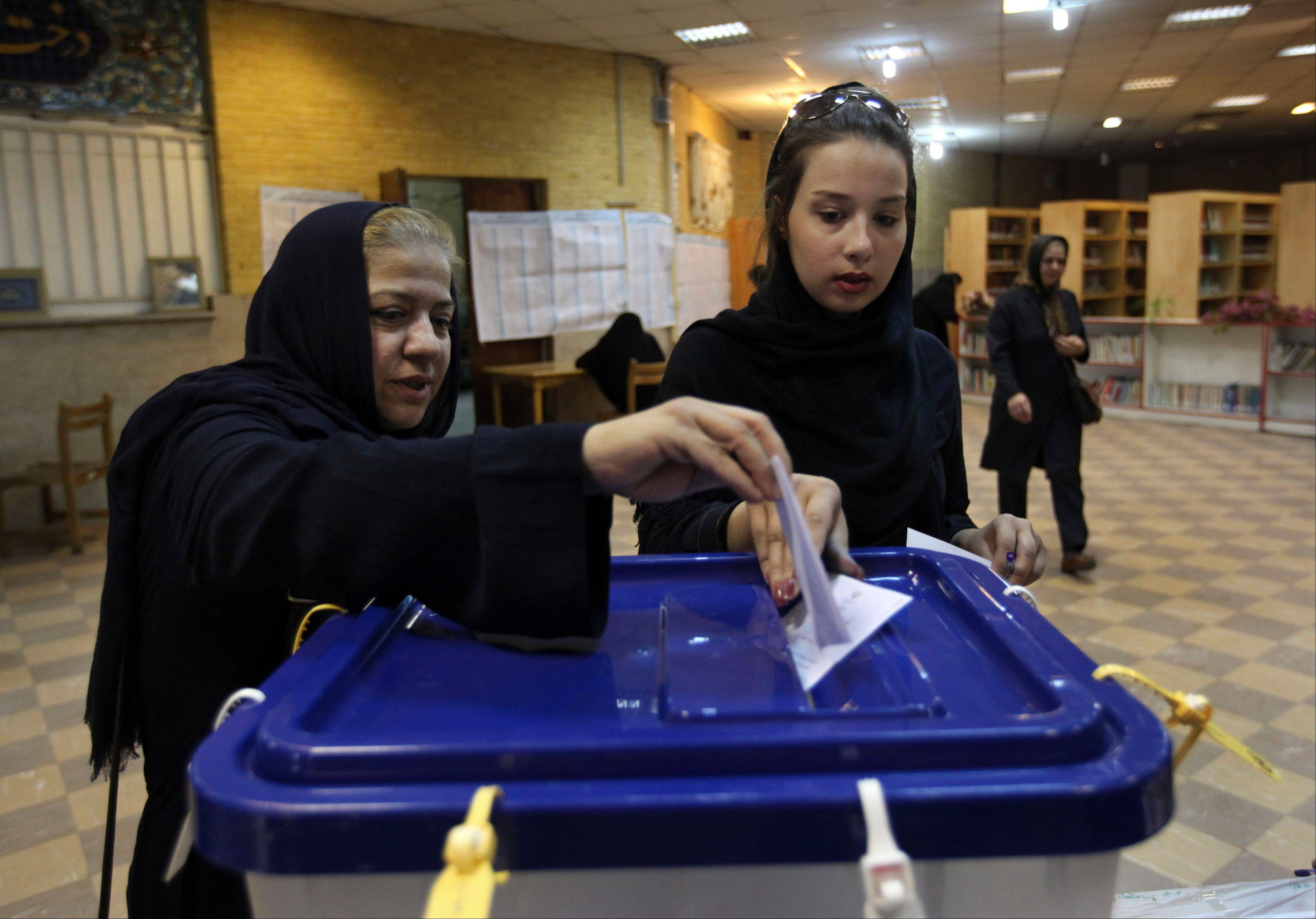 Two Iranian women cast their ballots during the presidential and municipal councils elections in a polling station in Tehran, Iran, Friday.