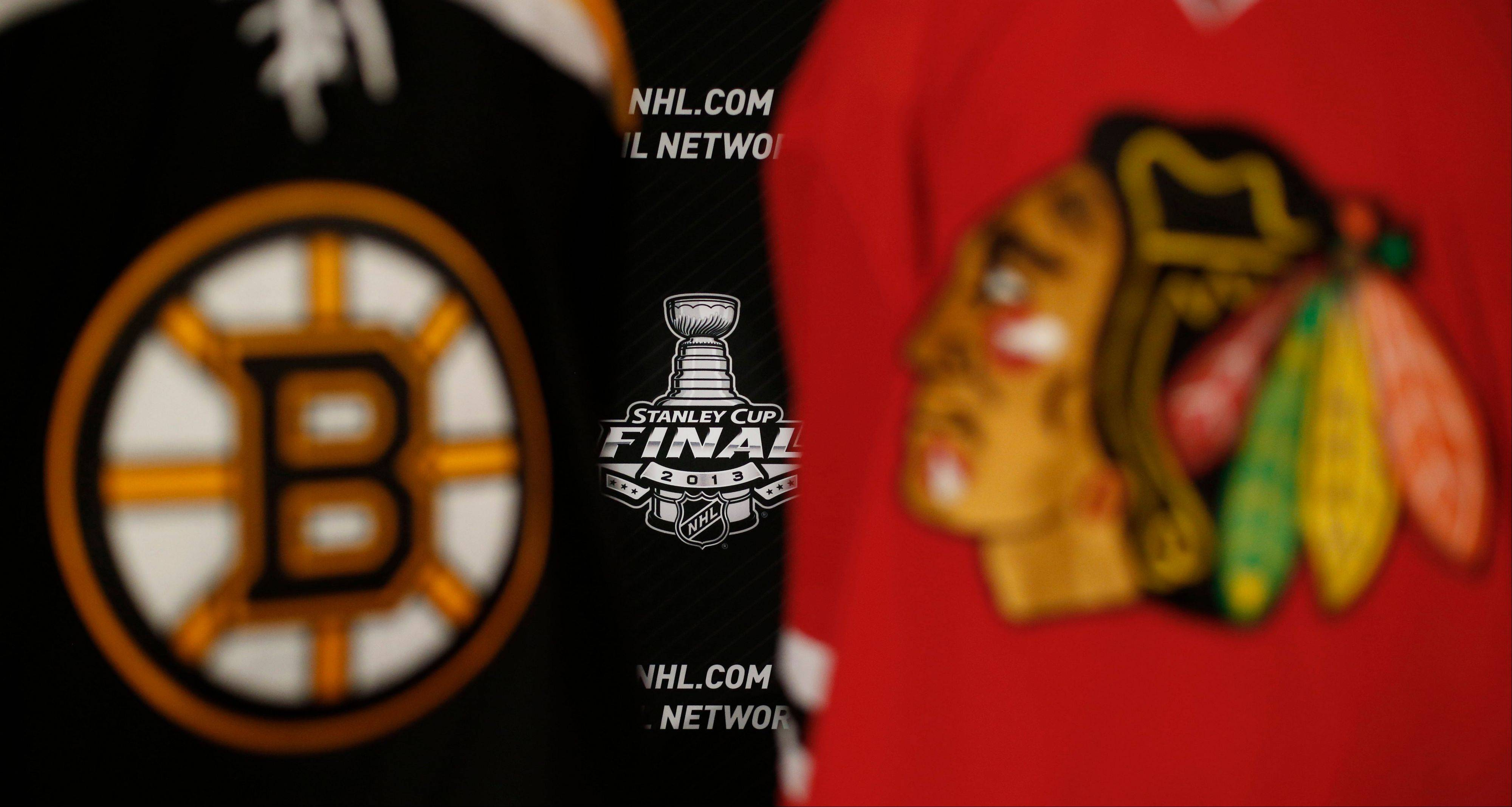 The 2013 NHL Stanley Cup log is seen between the sweaters of the Boston Bruins and the Blackhawks Tuesday in Chicago. The first game of the Stanley Cup is Wednesday at the United Center.
