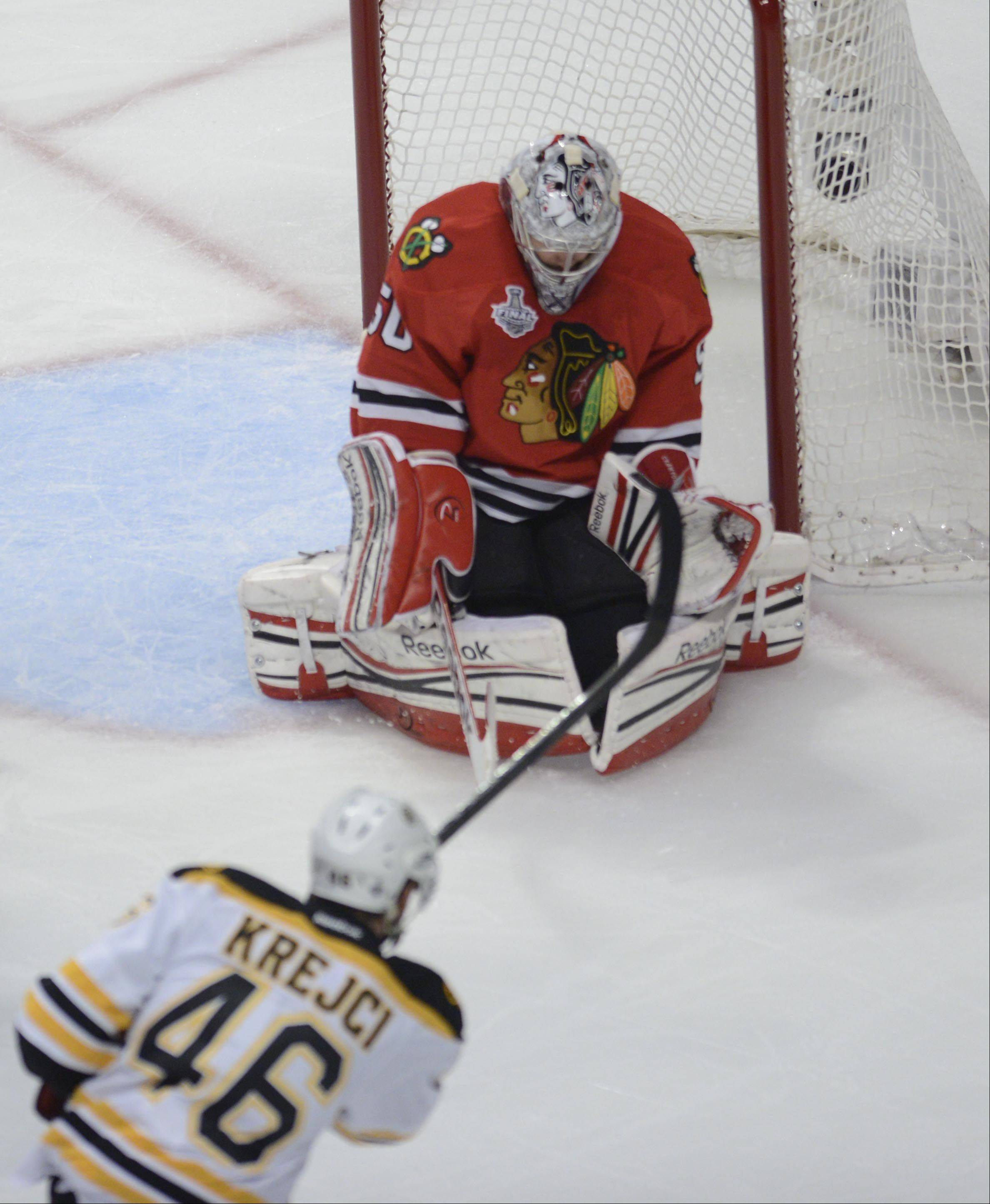 Chicago Blackhawks goalie Corey Crawford blocks and holds a shot by Boston Bruins center David Krejci in the first period during Game 1 of the Stanley Cup Finals Wednesday at the United Center in Chicago.