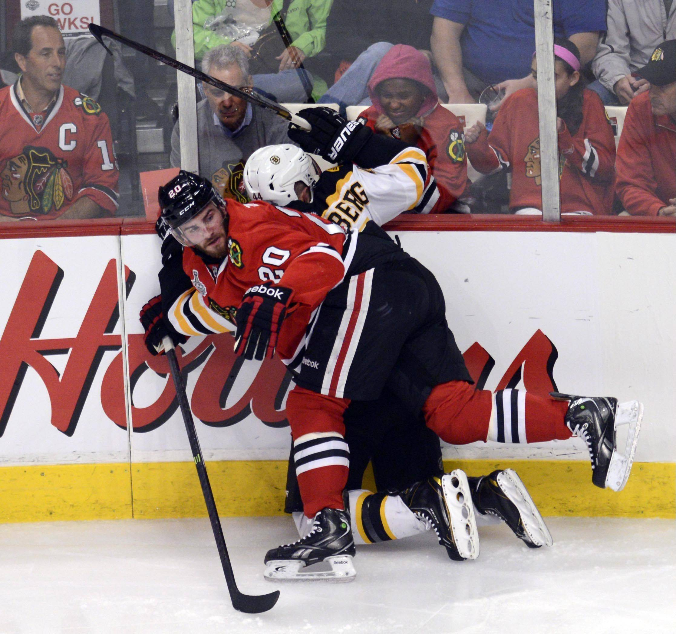 Blackhawks left wing Brandon Saad pins Boston Bruins defenseman Dennis Seidenberg to the boards in front of Chicago Mayor Rahm Emanuel during Game 1 of the Stanley Cup Final on Wednesday at the United Center in Chicago.