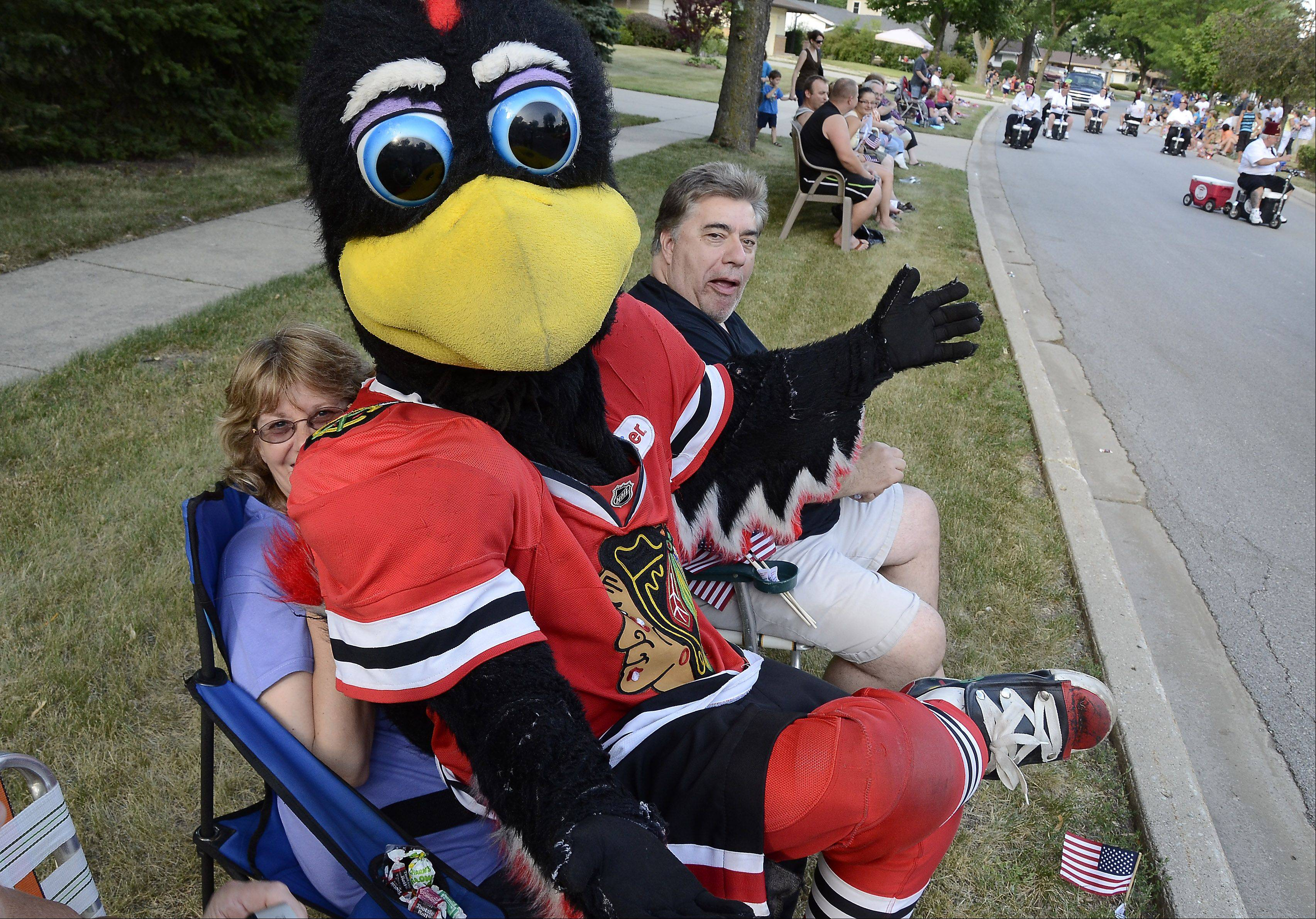 The Blackhawks Tommy Hawk, with Janeen and Ron Wojcik, of Hanover Park watch a previous Elk Grove Village Hometown Parade.