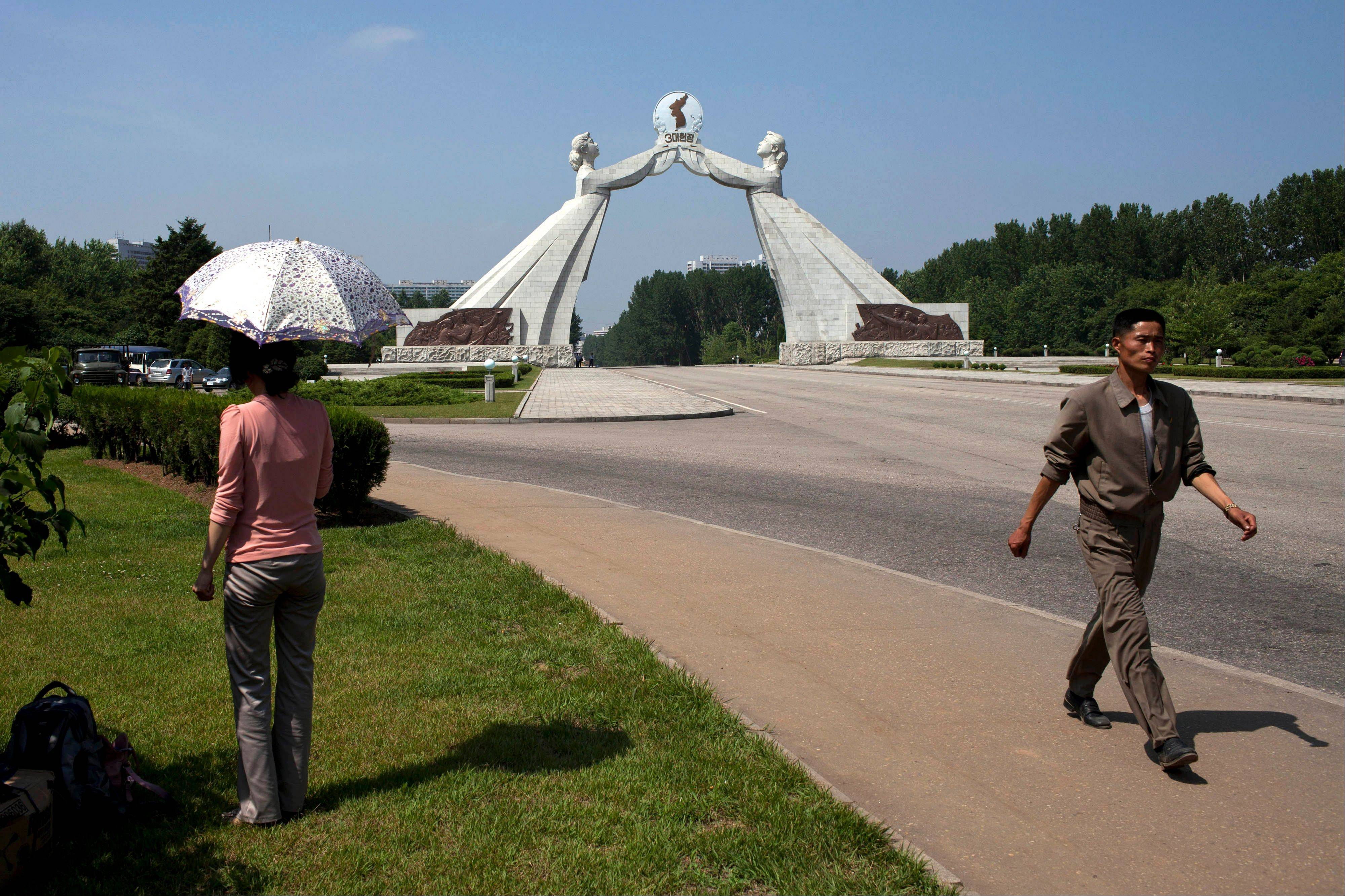 A woman rests under an umbrella while a man walks past her Saturday near a statue known as the Monument to the Three Charters for National Reunification, which symbolizes the hope for eventual reunification of the two Koreas, in Pyongyang, North Korea. In past years, the monument built over the road leading to South Korea has been the site of celebrations marking a joint reconciliation declaration signed by the two Koreas on June 15, 2000. This year�s events were canceled after high-level talks between the Seoul and Pyongyang governments, the first in six years, were called off earlier in the week.