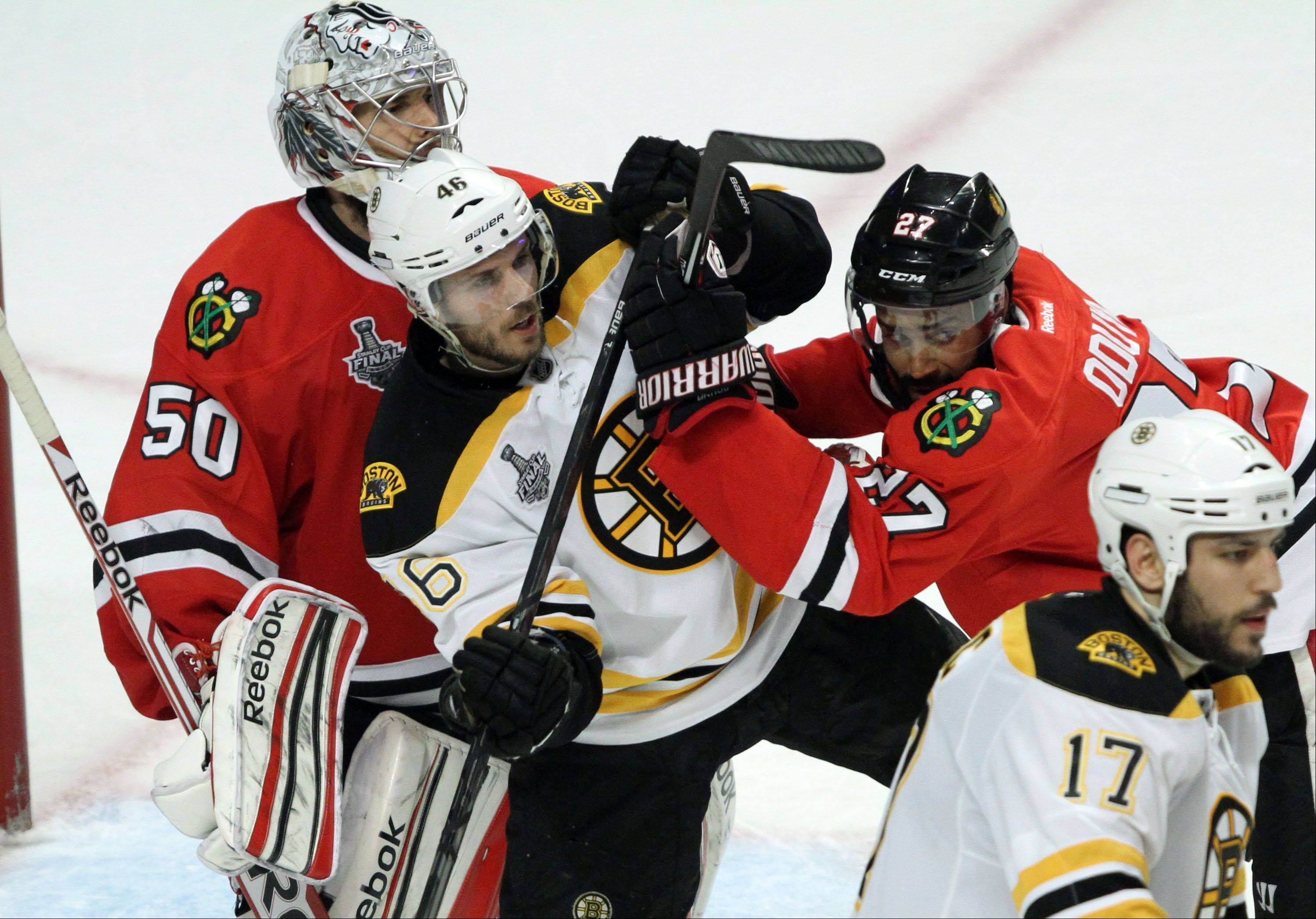 Blackhawks defenseman Johnny Oduya muscles Boston Bruins left wing Kaspars Daugavins during Saturday�s Game 2 of the Stanley Cup Final at United Center.