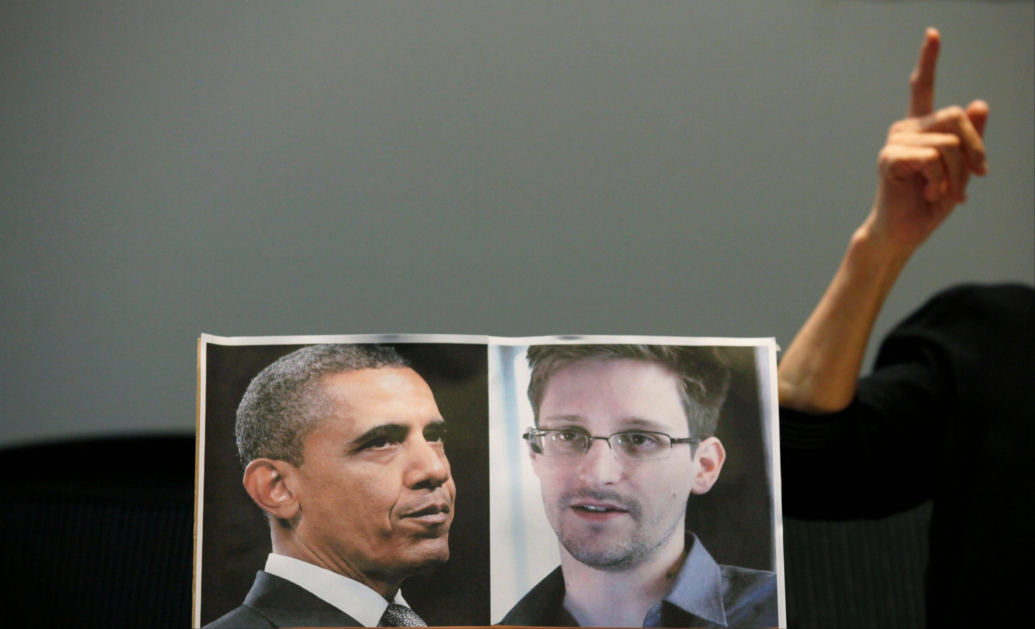 Pro-democractic legislator Claudia Mo Man-ching speaks next to a picture of U.S. President Barack Obama and Edward Snowden during a news conference Friday in Hong Kong. Two lawmakers in Hong Kong said they had written to President Obama to try to persuade him not to bring charges against the former US intelligence contractor Snowden.
