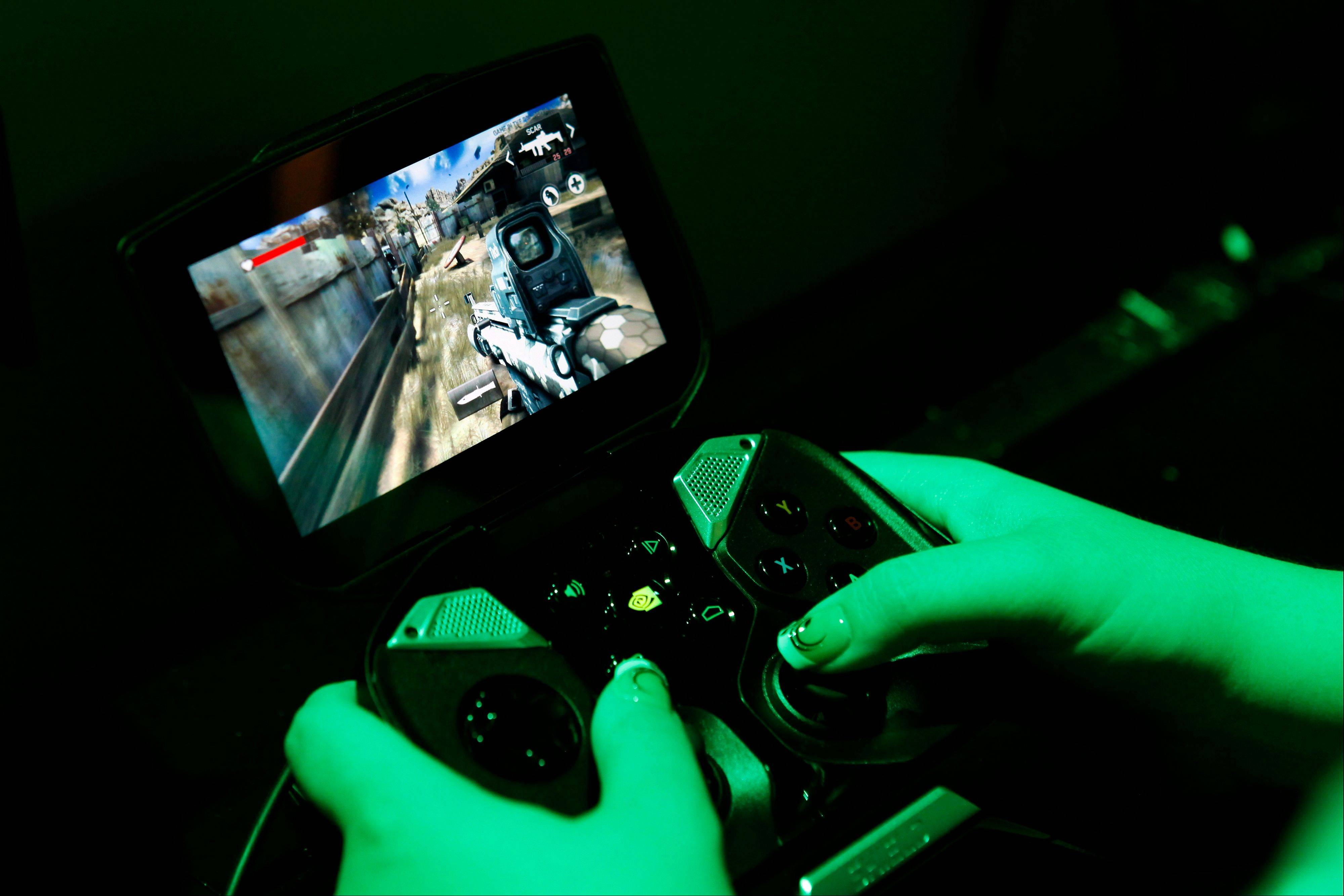 An attendee plays on Nvidia Corp.'s Nvidia Shield handheld game console at the company's booth during the E3 Electronic Entertainment Expo in Los Angeles, California, U.S., on Wednesday, June 12, 2013. E3, a trade show for computer and video games, draws professionals to experience the future of interactive entertainment as well as to see new technologies and never-before-seen products.