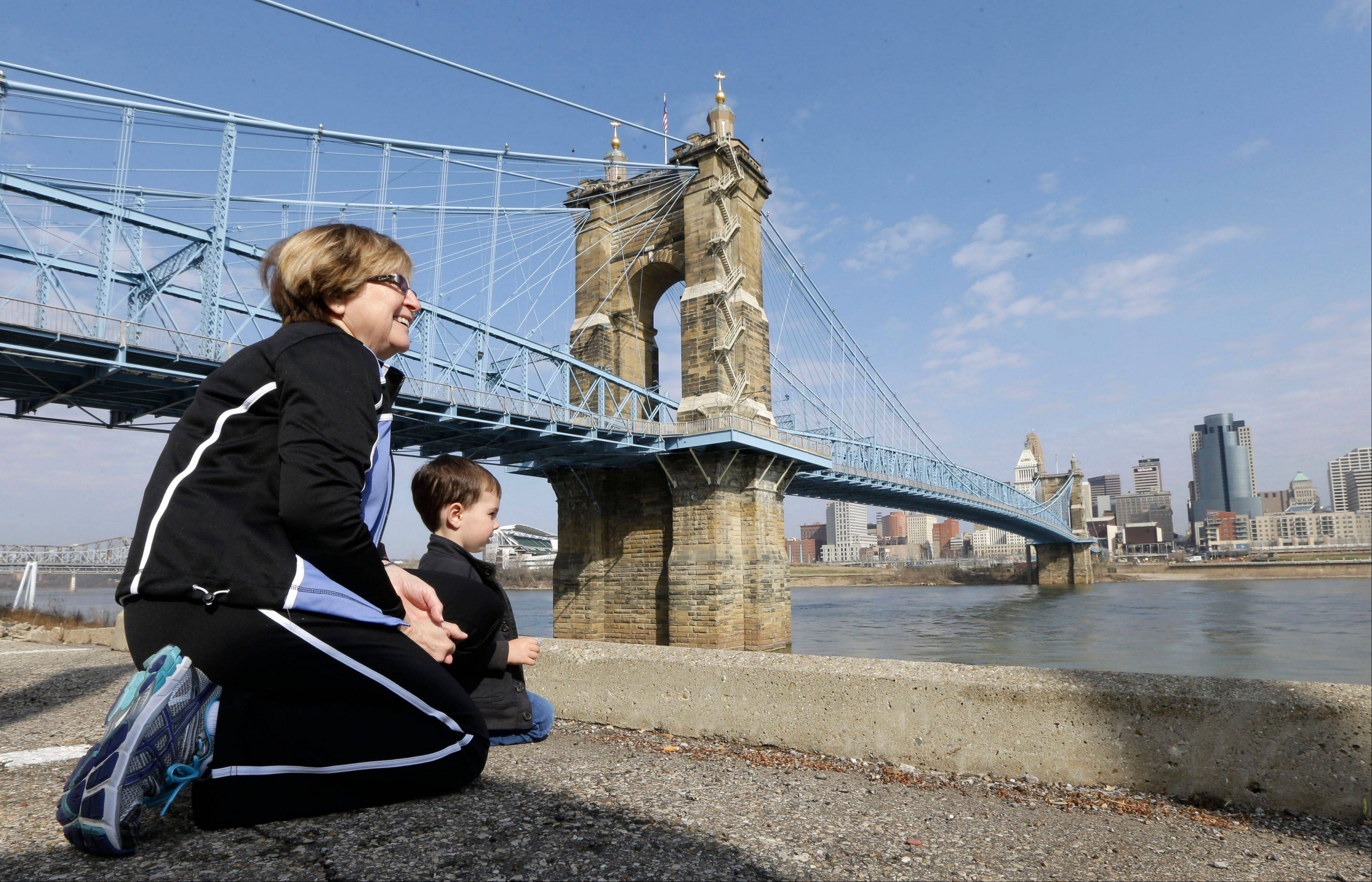 Yvonne Parmley kneels with her grandson, Finley MacKay, as they look toward downtown Cincinnati next to the Roebling Suspension Bridge over the Ohio River in Covington, Ky.