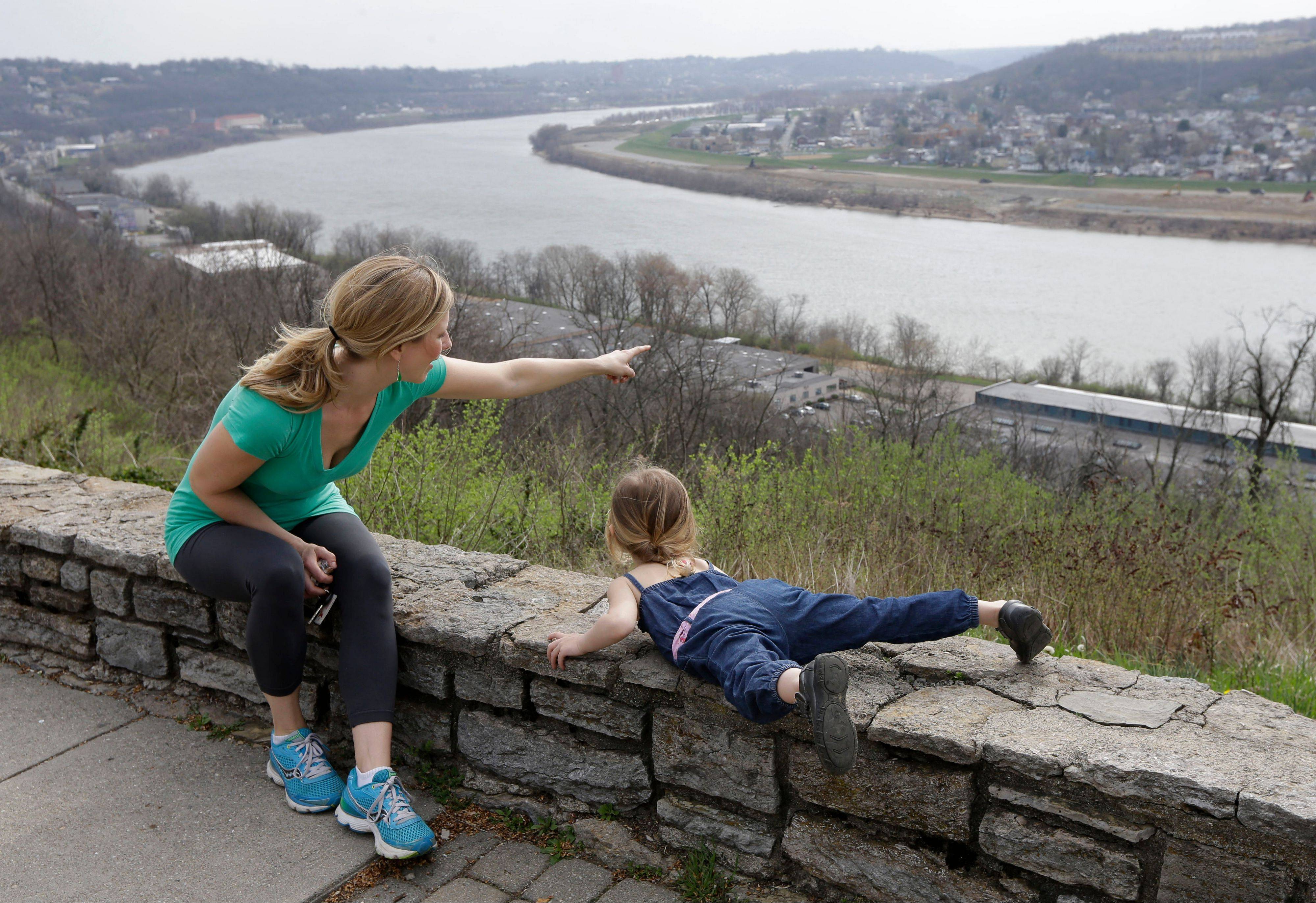 Rachel Mardis points out over the Ohio River toward northern Kentucky with her daughter Skylar, 2, at the Eden Park Overlook in Cincinnati.