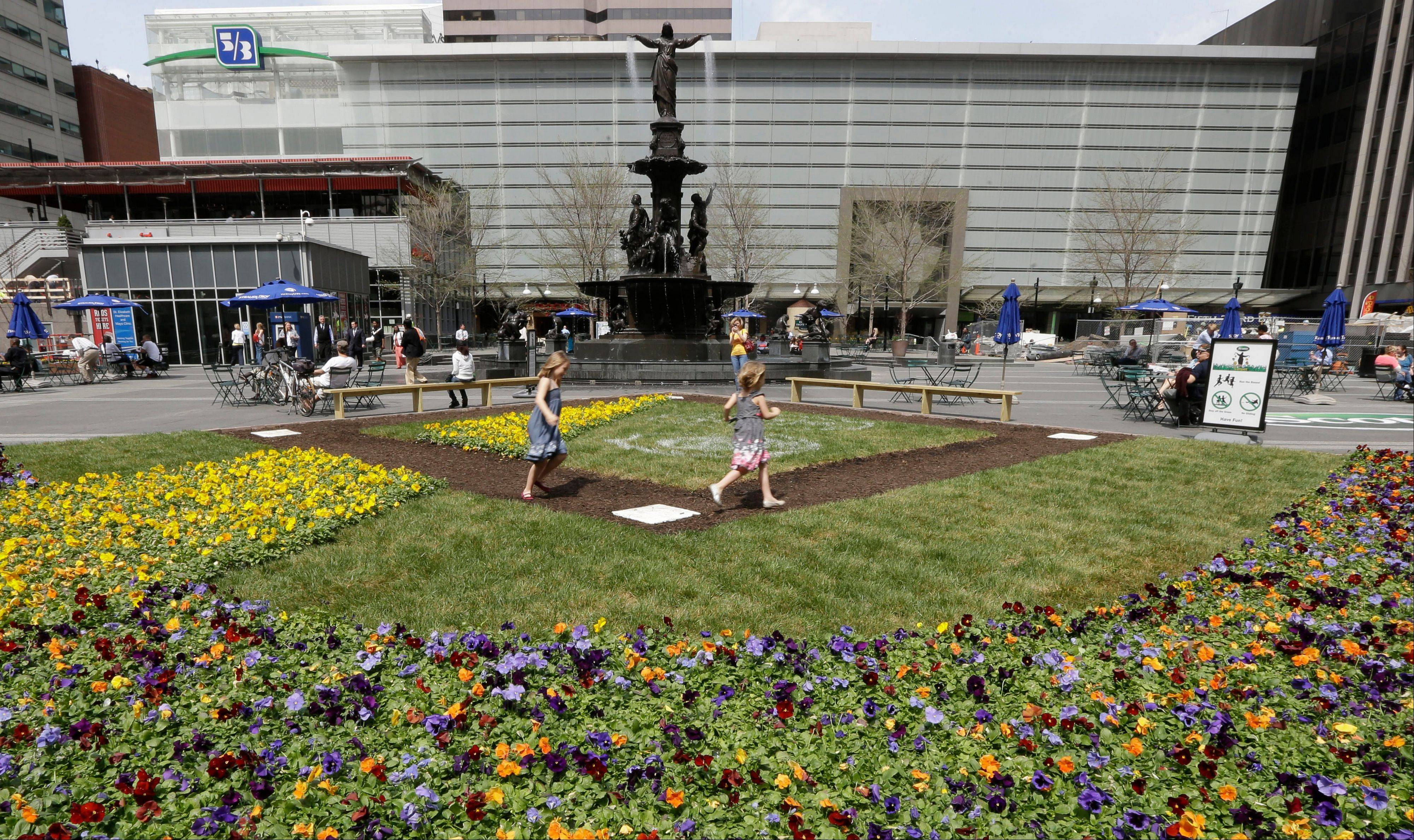 Hannah Bailey, left, runs the bases with sister Eva Bailey on a baseball diamond floral display set up on Fountain Square in Cincinnati.