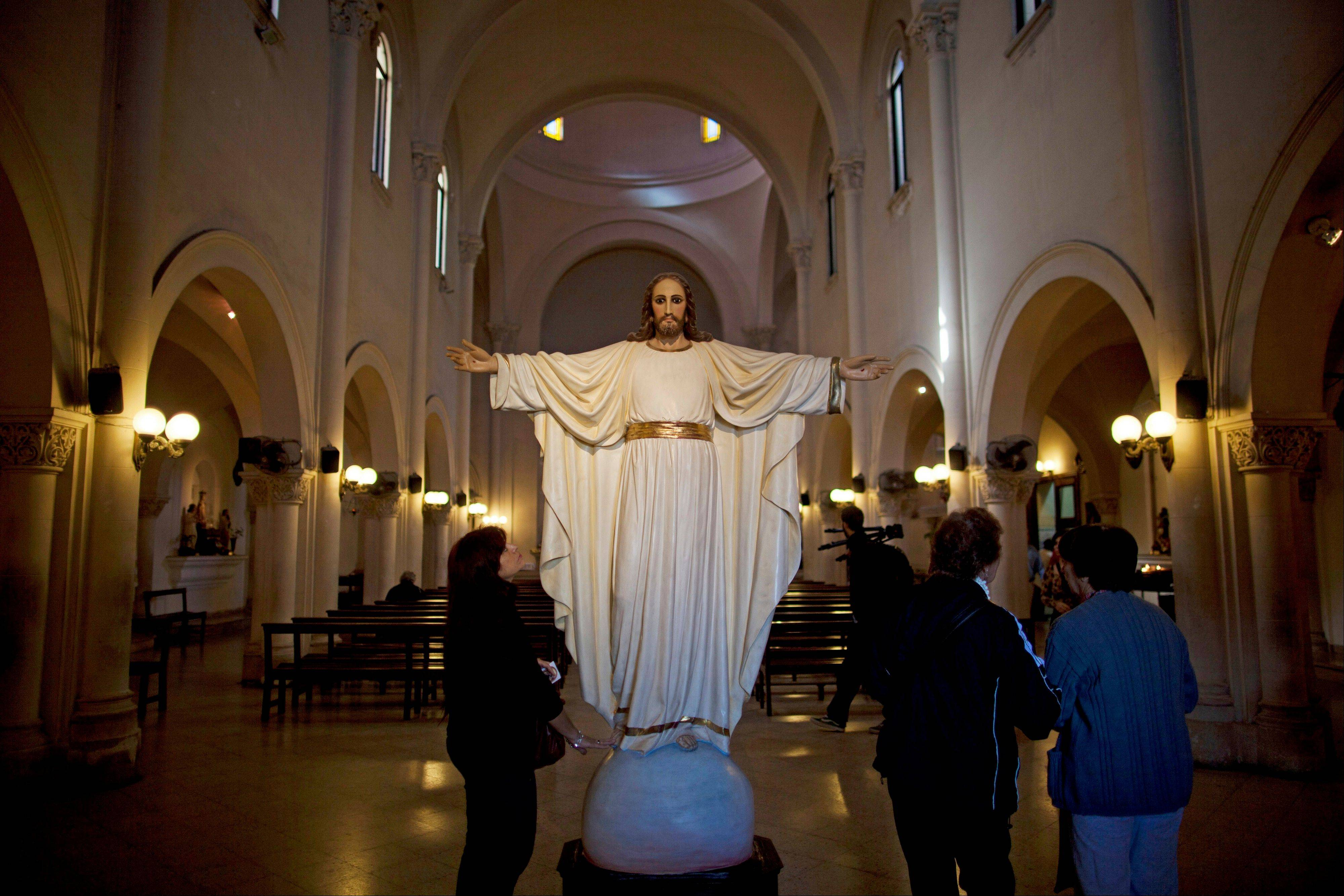 A woman looks up at a statue of Jesus Christ in the San Jose del Talar parish in Buenos Aires, Argentina. With an Argentine on the throne of St. Peter, the South American country's capital city has launched a series of guided tours.
