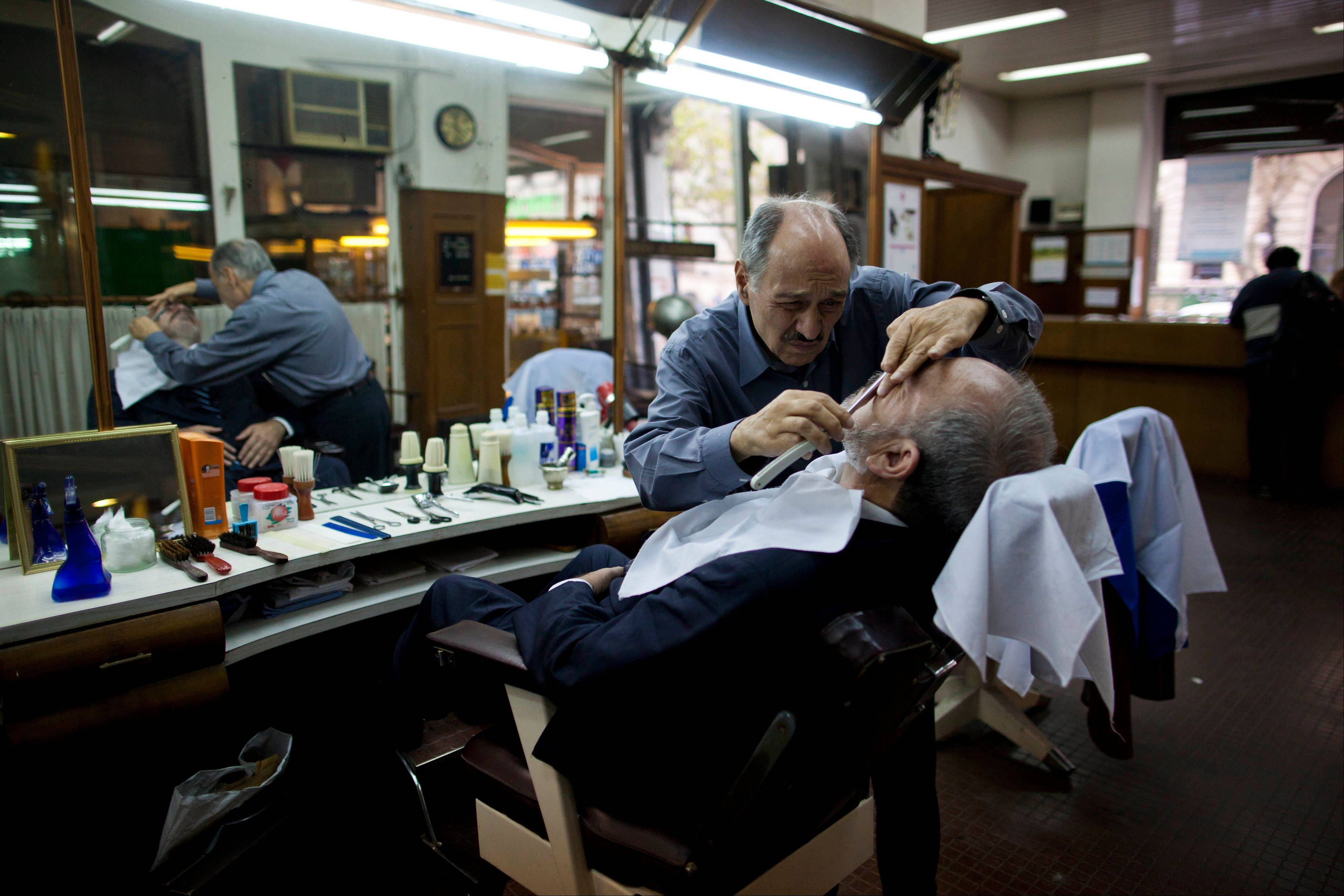 Barber Mario Saliche shaves a customer at the Romano hairdresser and barber shop in Buenos Aires. Guided tours include the barber shop, where Archbishop Jorge Bergoglio had a monthly haircut for 20 years.
