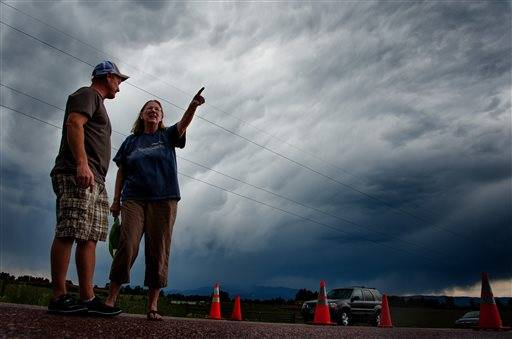 Jasen Dill, left, and Judy Pohlod discuss returning to their homes, which made it through the Black Forest fire safely, as a storm passes overhead at the corner of Hodgen Road and Highway 83 Friday, June 14, 2013 in Colorado Springs, Colo.