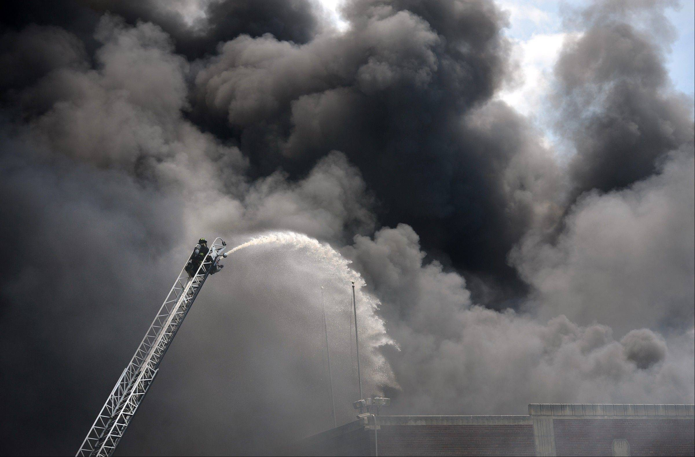 Firefighters spray water on a large fire Saturday in Indianapolis. An estimated 150 firefighters were battling the blaze Saturday afternoon in the building about one mile southwest of the city's downtown.