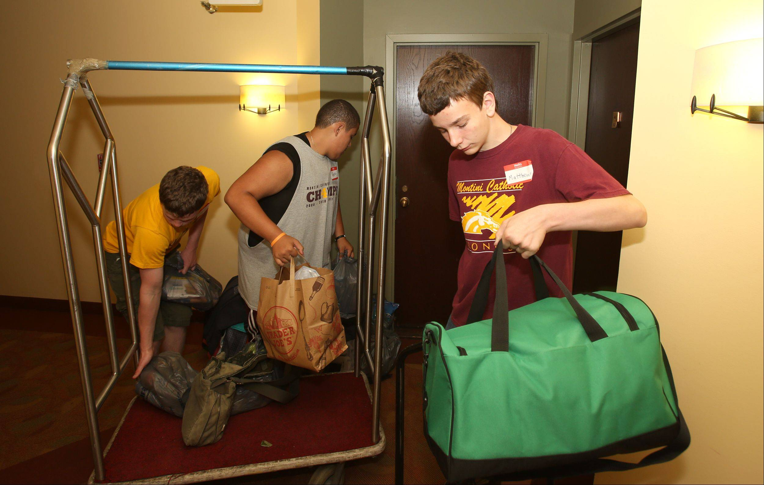Montini Catholic High School students Matthew Ernat, right, Sam Detmers and Robert Garcia help flood-displaced residents move back to the Towers at Four Lakes in Lisle on Saturday. Flooding forced residents of the apartments to evacuate in April.