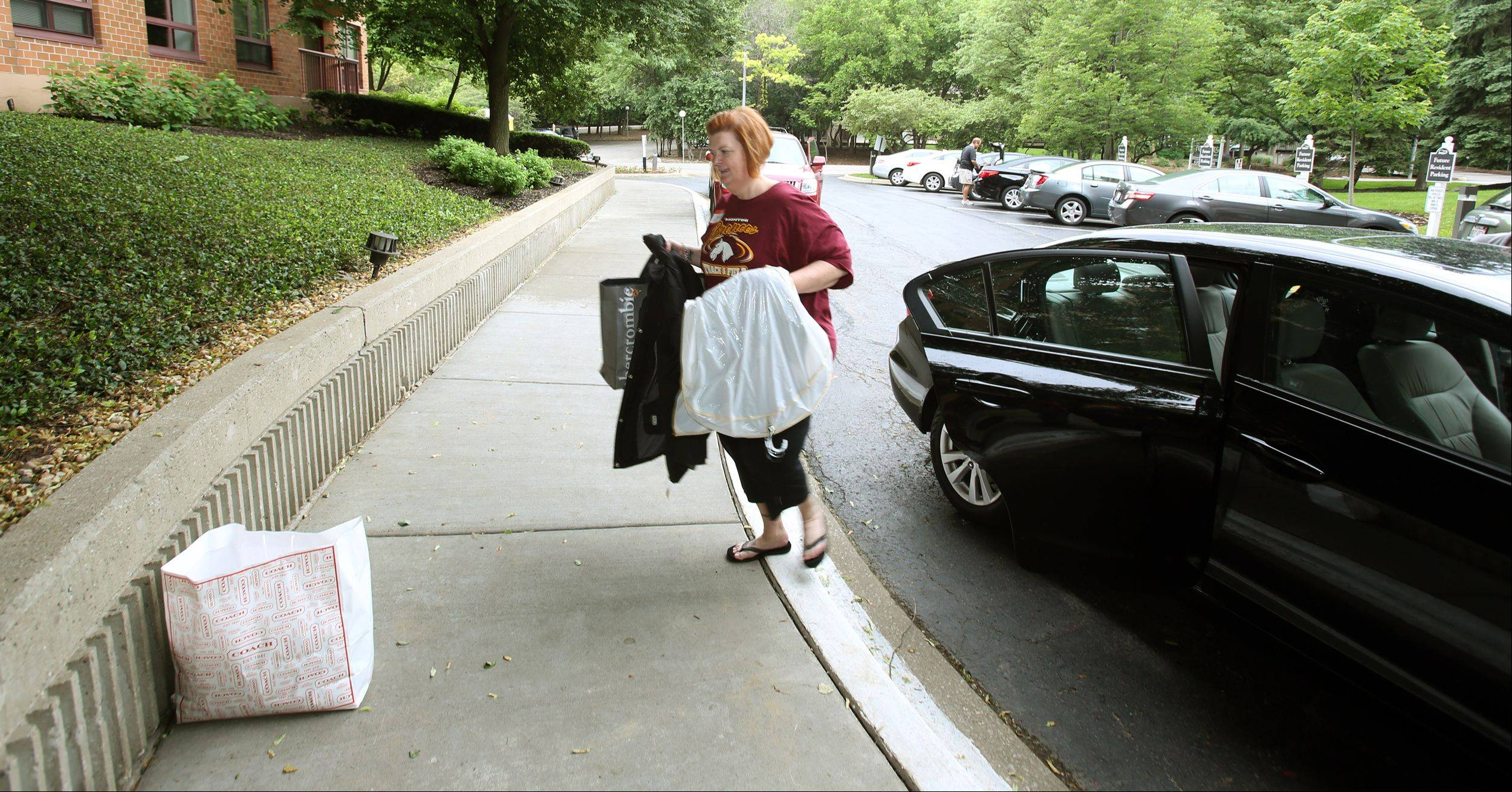 Volunteer Debra Schulz helps flood-displaced residents move back to the Towers at Four Lakes in Lisle on Saturday. Flooding forced residents of the apartments to evacuate in April.
