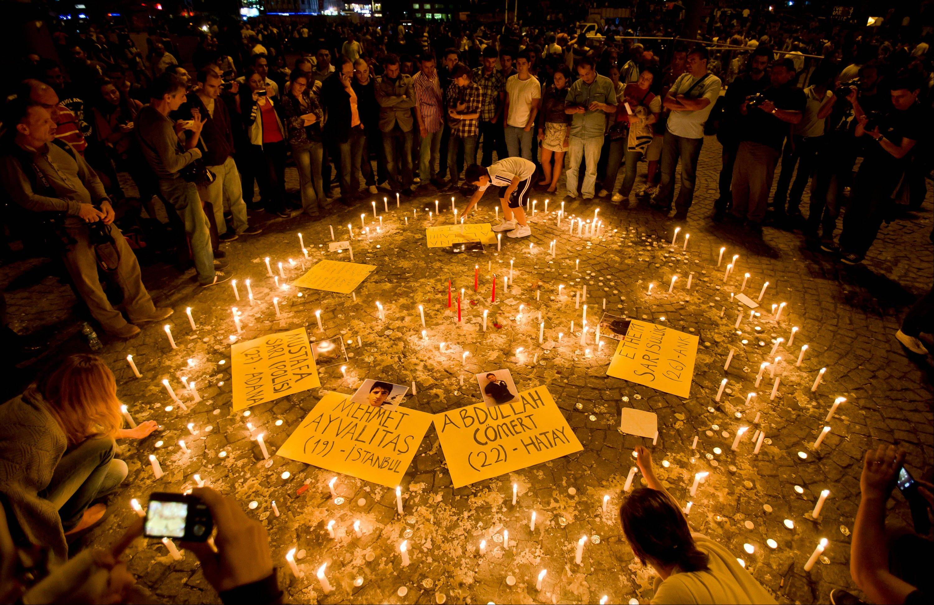 People light candles for the victims of the protests at Taksim square, in Istanbul, early Saturday. Protesters took to the streets late Saturday after an occupying camp of protesters was run out of Gezi park by riot police.