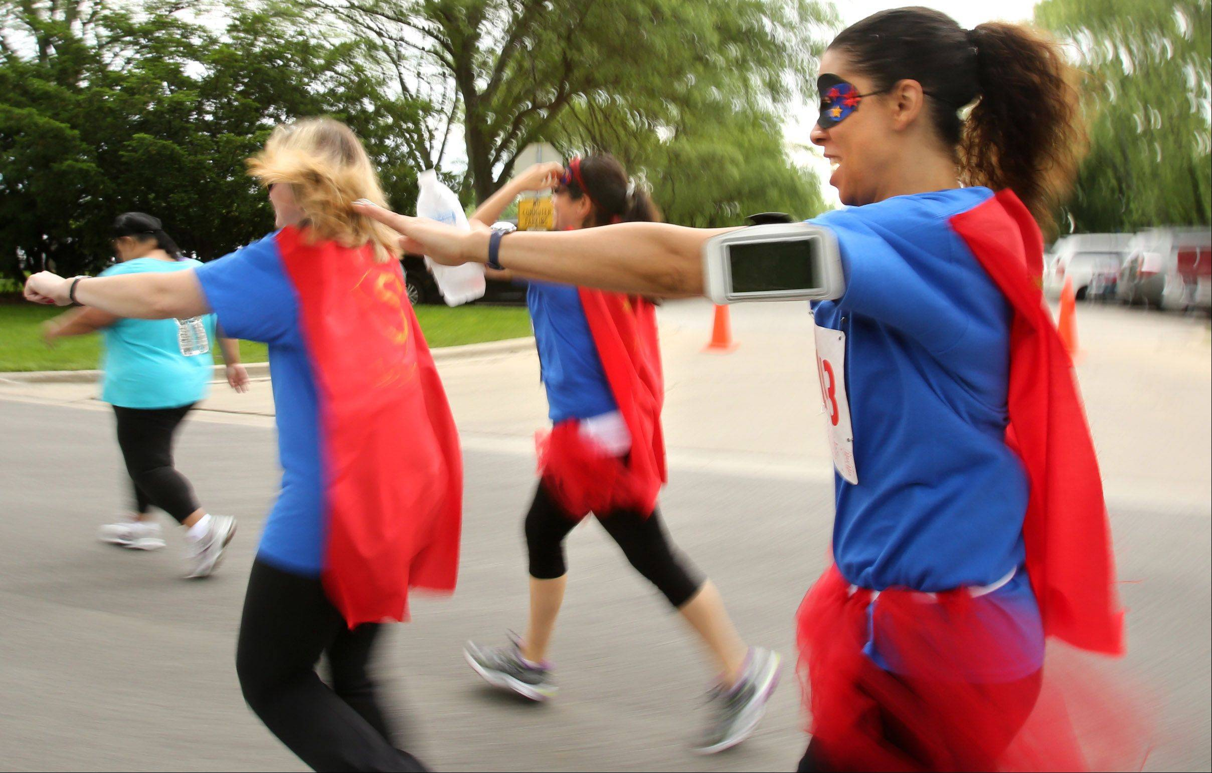 Roz Moore of Mount Prospect runs with a group of friends wearing homemade superhero costumes in Mount Prospect Park District's Super 5K Run at Lions Memorial Park on Saturday. Participants were encouraged to dress in their favorite superhero costumes.