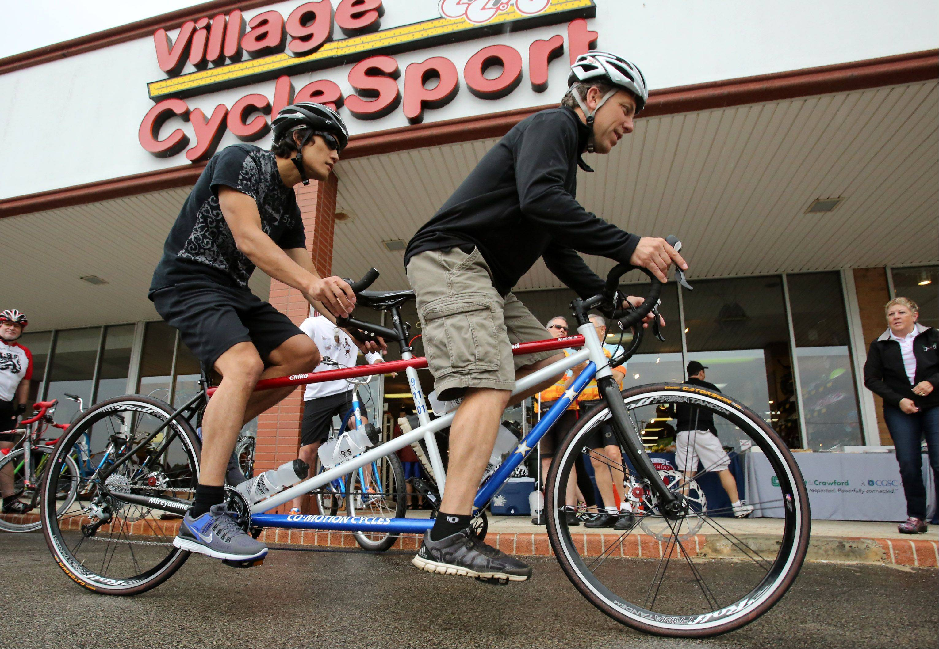 U.S. Army veteran Steve Baskis, left, rides a new competitive tandem bike with Village CycleSport co-owner Vince Boyer Saturday after the bike was donated to him by insurance company Swett & Crawford.