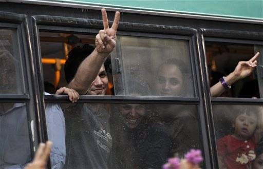 Passengers in a public bus flash victory signs in a reaction of supporters of the Iranian presidential candidate Hasan Rowhani, as they attend a celebration gathering, in Tehran, Iran, Saturday, June 15, 2013. Moderate cleric Hasan Rowhani was declared the winner of Iran's presidential vote on Saturday after gaining support among many reform-minded Iranians looking to claw back a bit of ground after years of crackdowns