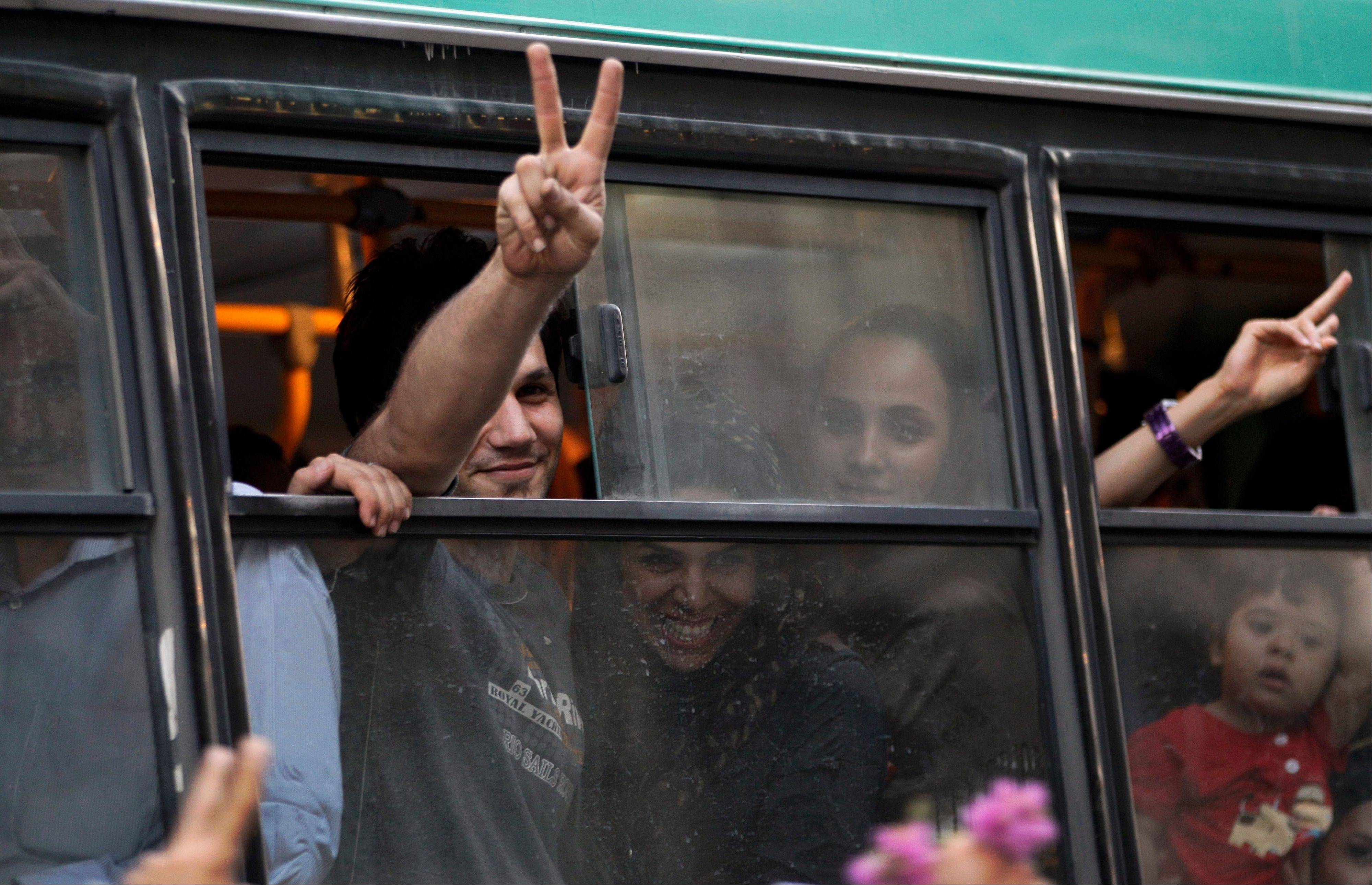 Passengers in a public bus flash victory signs in a reaction of supporters of the Iranian presidential candidate Hasan Rowhani, as they attend a celebration gathering Saturday in Tehran. Moderate cleric Hasan Rowhani was declared the winner of Iran's presidential vote after gaining support among many reform-minded Iranians looking to claw back a bit of ground after years of crackdowns.