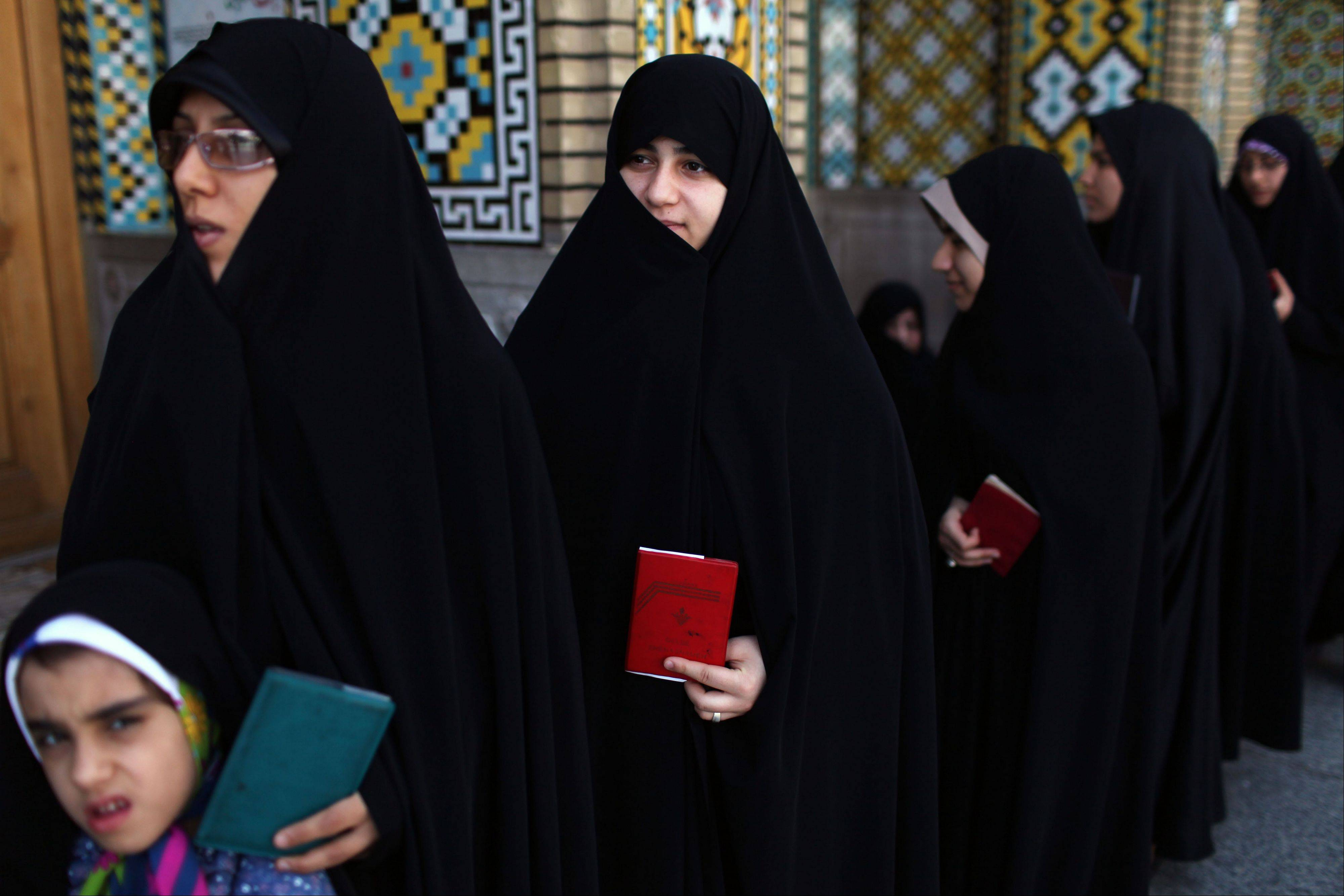 Iranian women wait in line at a polling station Friday to vote during presidential elections.