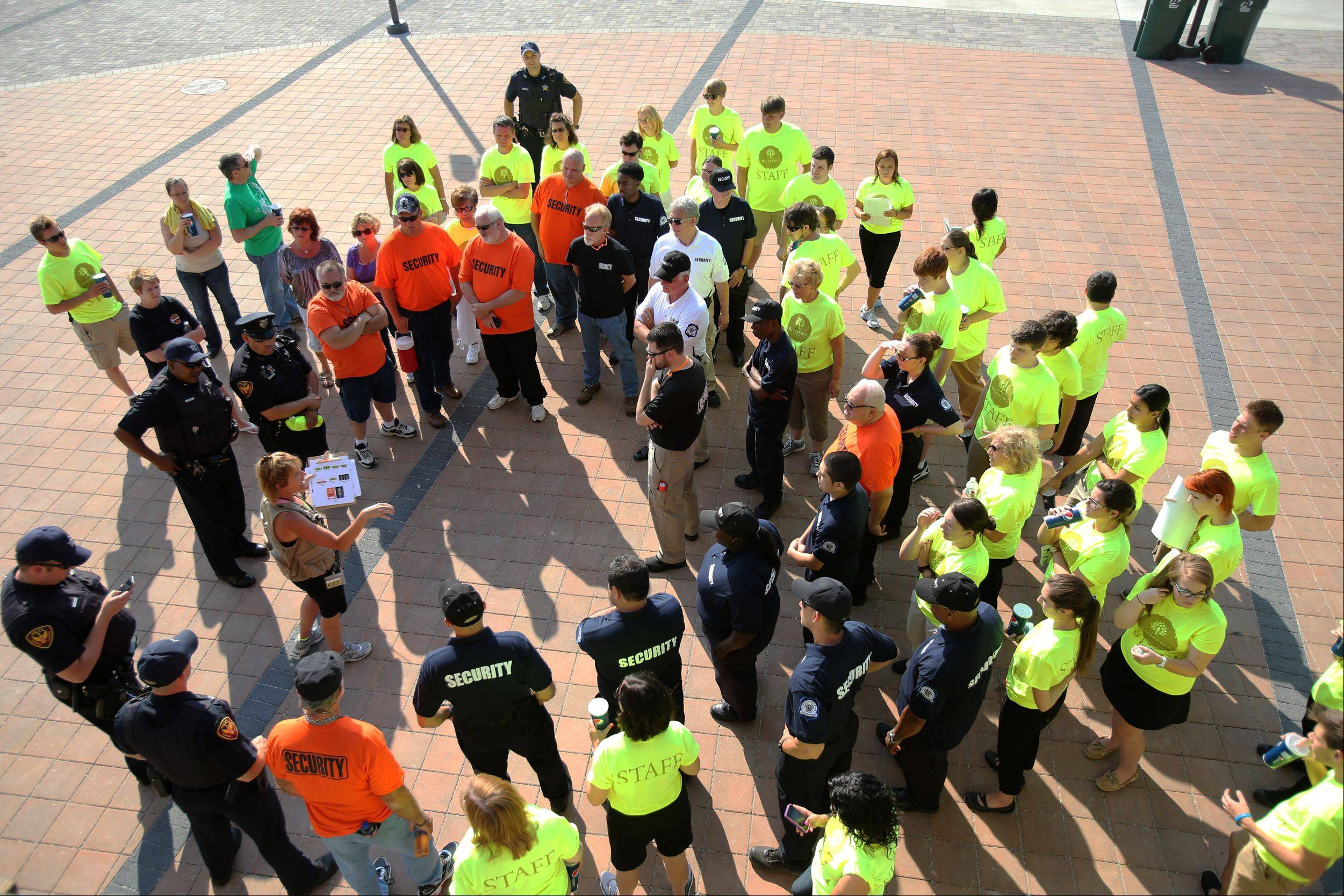 Workers receive instructions before the opening night of RiverEdge Park, coinciding with the 17th annual Blues on the Fox festival.