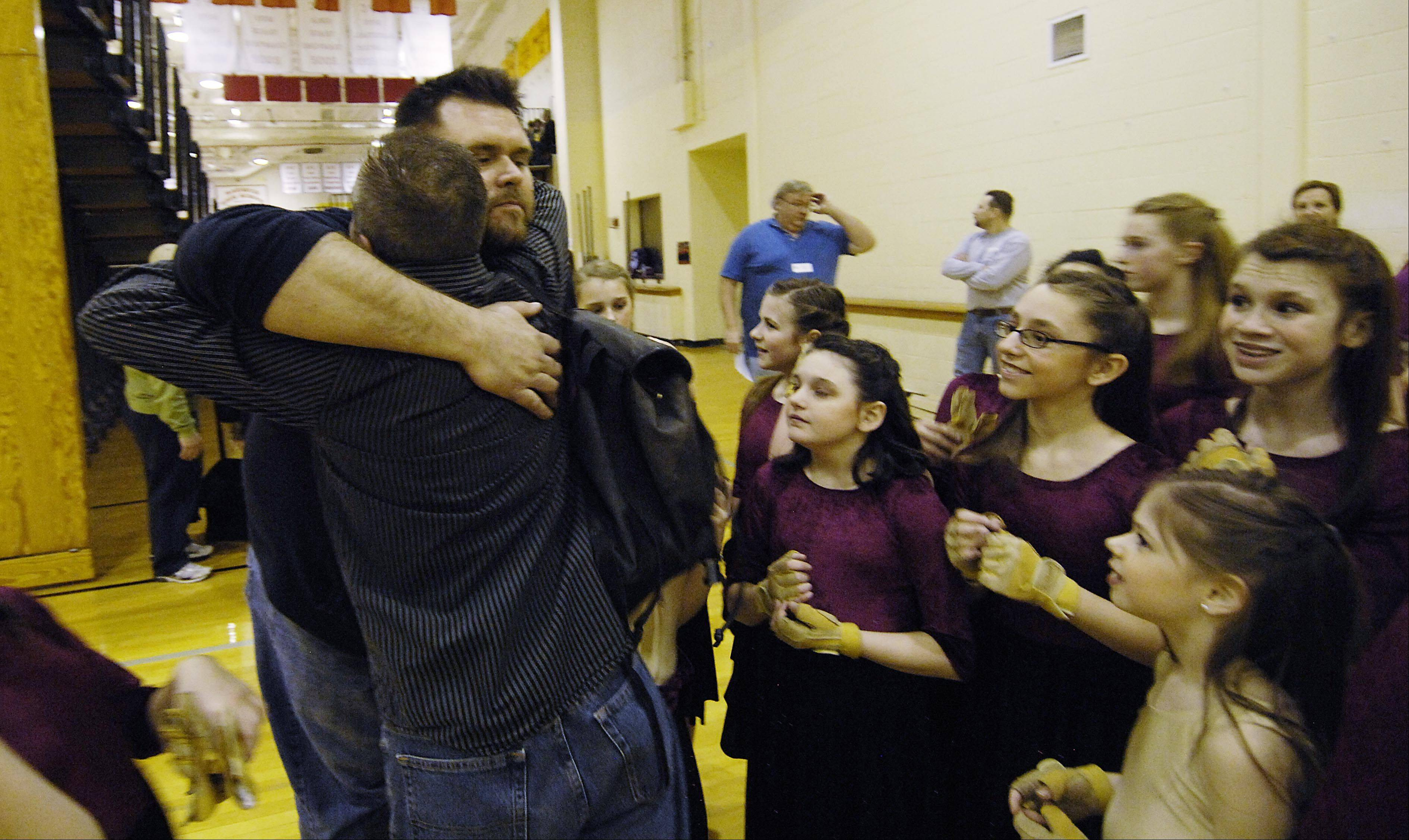 Assistant Director Don Wiles hugs Eric Hall, director of Allegiance Youth Color Guard of Dundee, after a performance as the cadet squad watches. The performing arts group incorporates dance, theater, props, and traditional color guard marching into a judged, 3-minute competition performance.