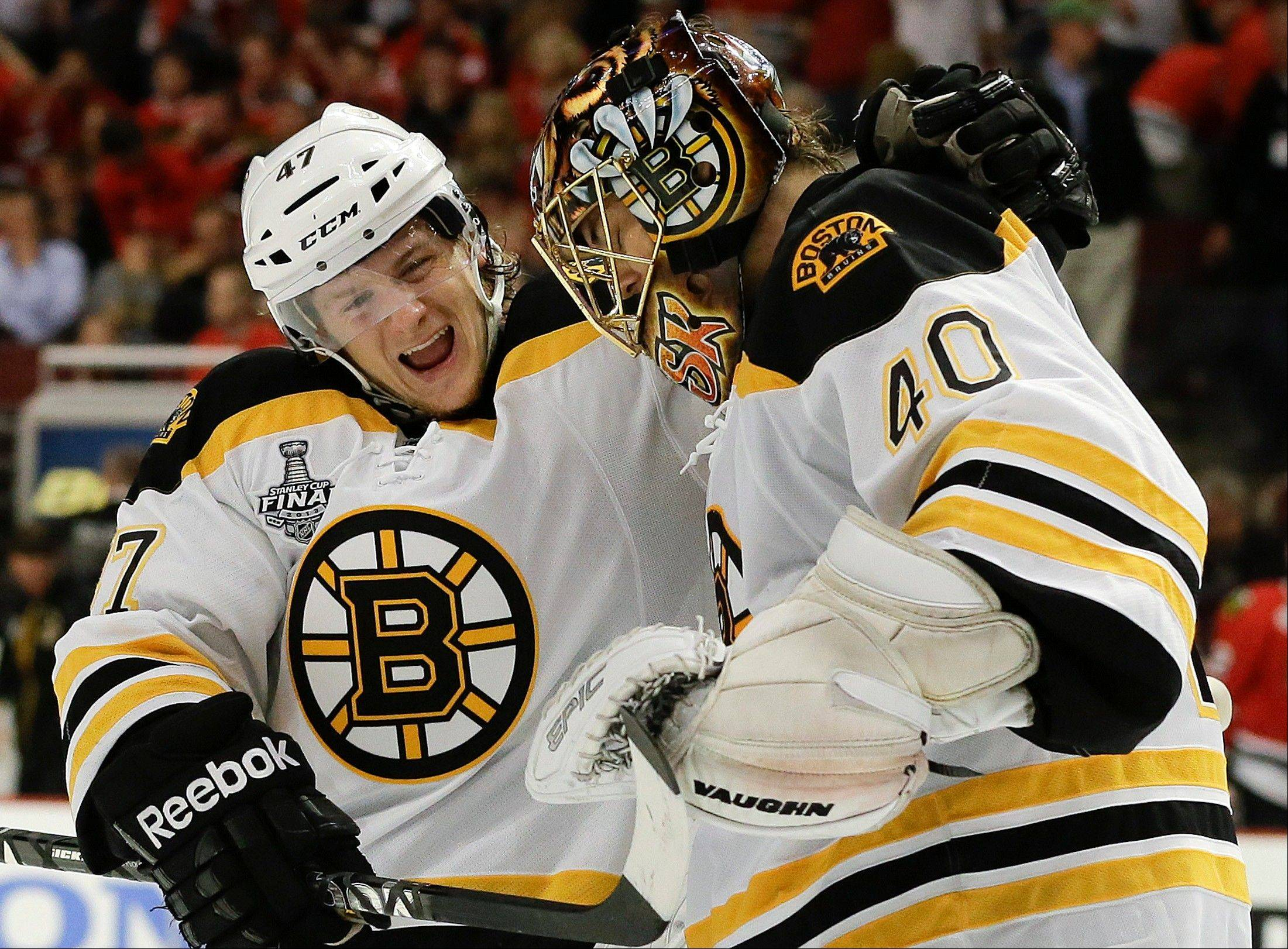 Boston Bruins defenseman Torey Krug celebrates Saturday with goalie Tuukka Rask after the Bruins beat the Hawks in overtime at United Center.