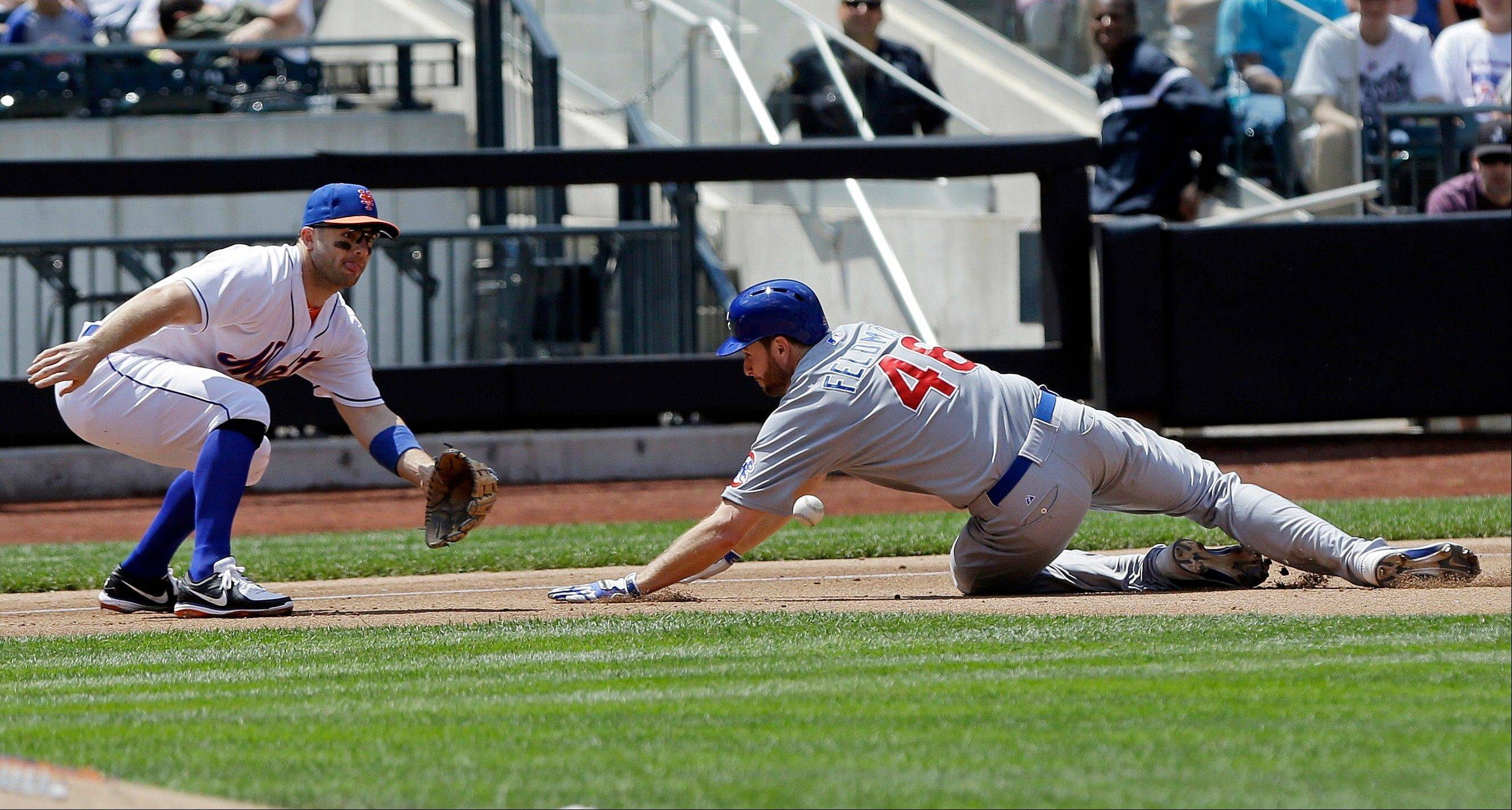 Chicago Cubs' Scott Feldman (46) slides in safely at third base as New York Mets third baseman David Wright (5) waits for the ball during the fourth inning of a baseball game Saturday, June 15, 2013, in New York. Feldman advanced from first base on a single by Darwin Barney.