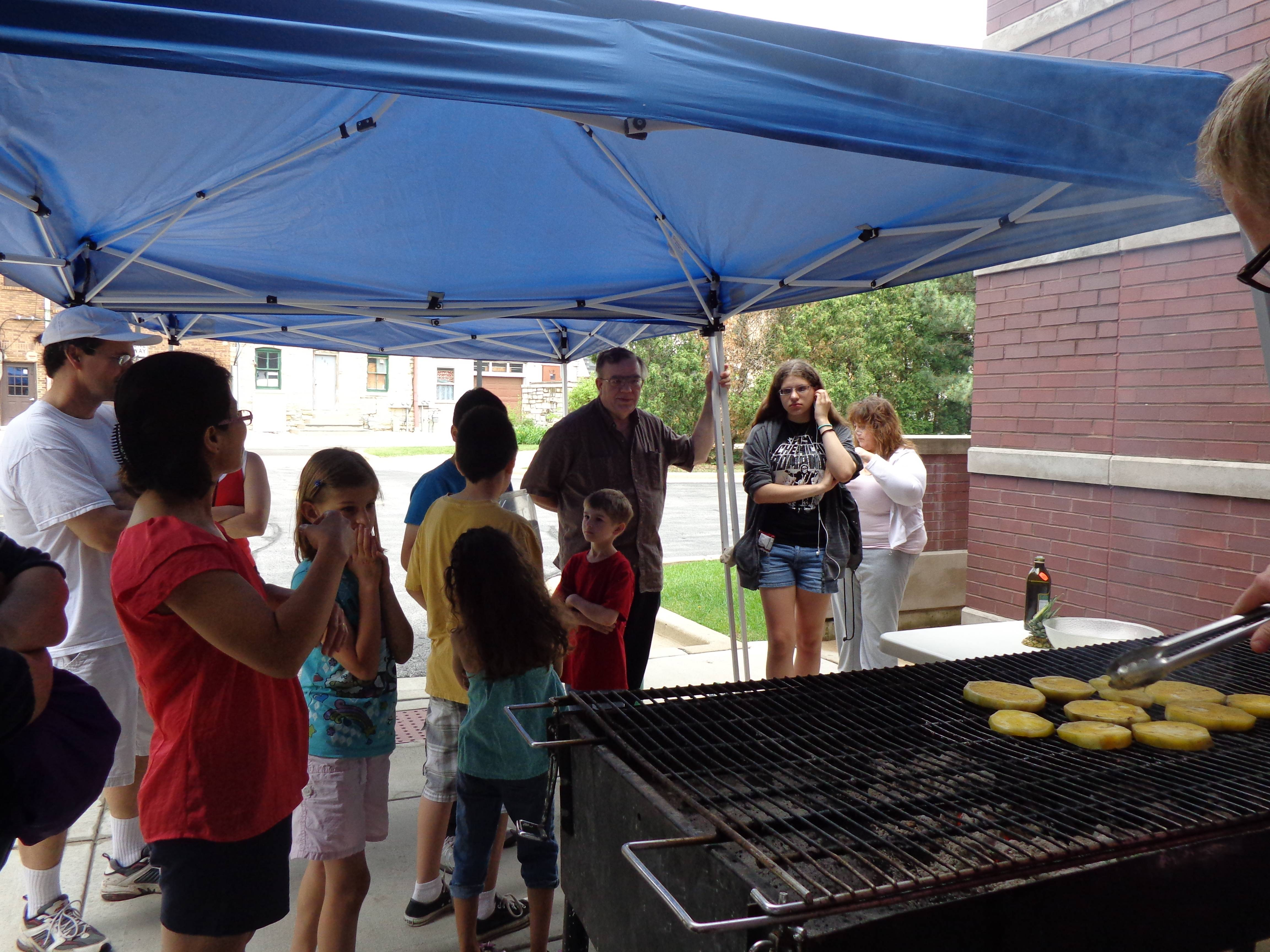 West Chicago library patrons stay dry while watching a grilling demonstration by Chef David Esau as part of the Father's Day Cookout program on Saturday.