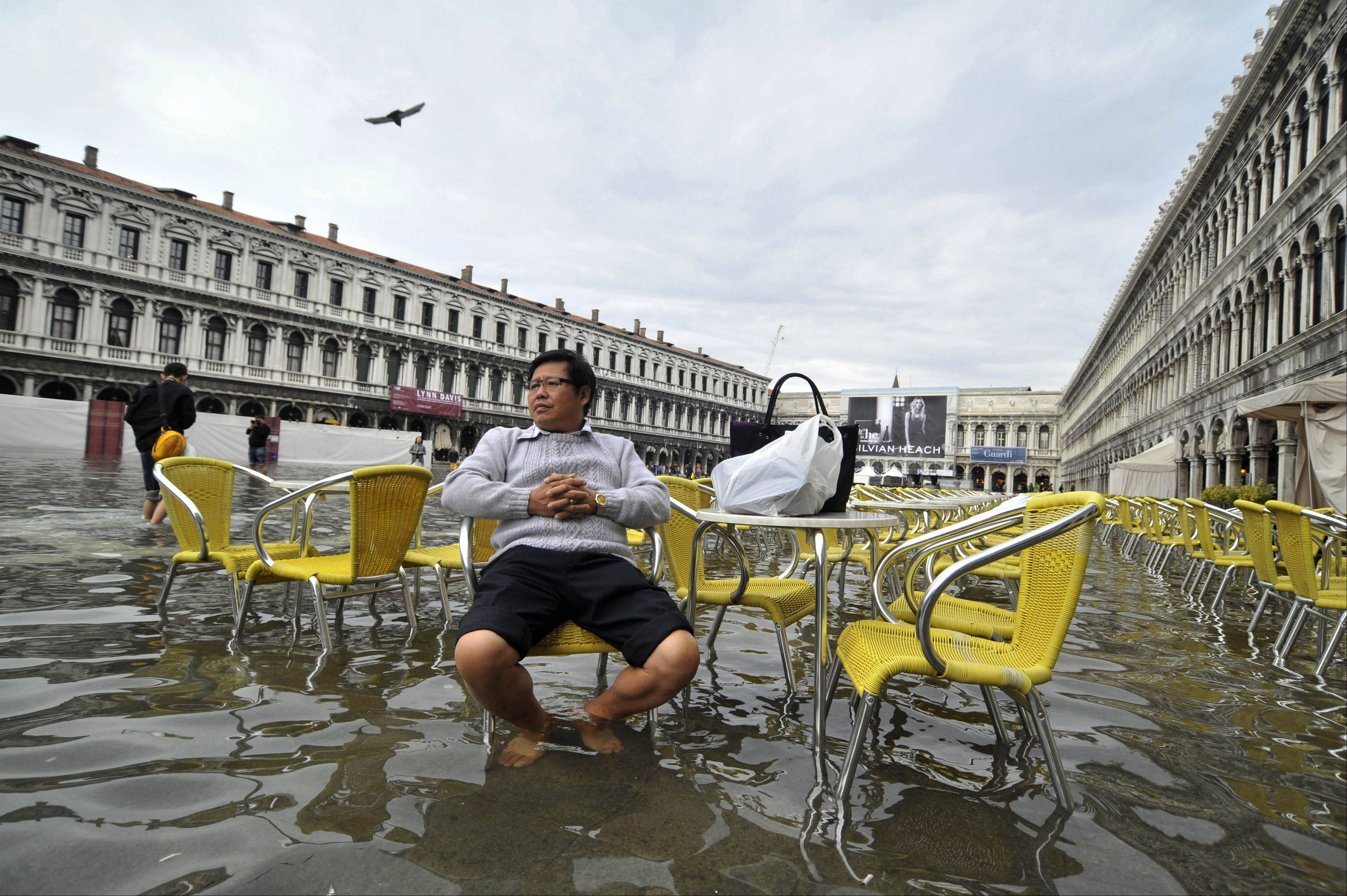 A tourist sits outside a cafe in a flooded St. Mark square as high tides reached three feet above sea level, partly flooding the city of Venice, Italy, Oct. 15, 2012. The Lagoon City, a system of islands built into a river delta, is extremely vulnerable to rising sea levels. At the same time it is experiencing a lowering of the sea floor. The constant flooding puts the city�s considerable architectural treasures at risk.