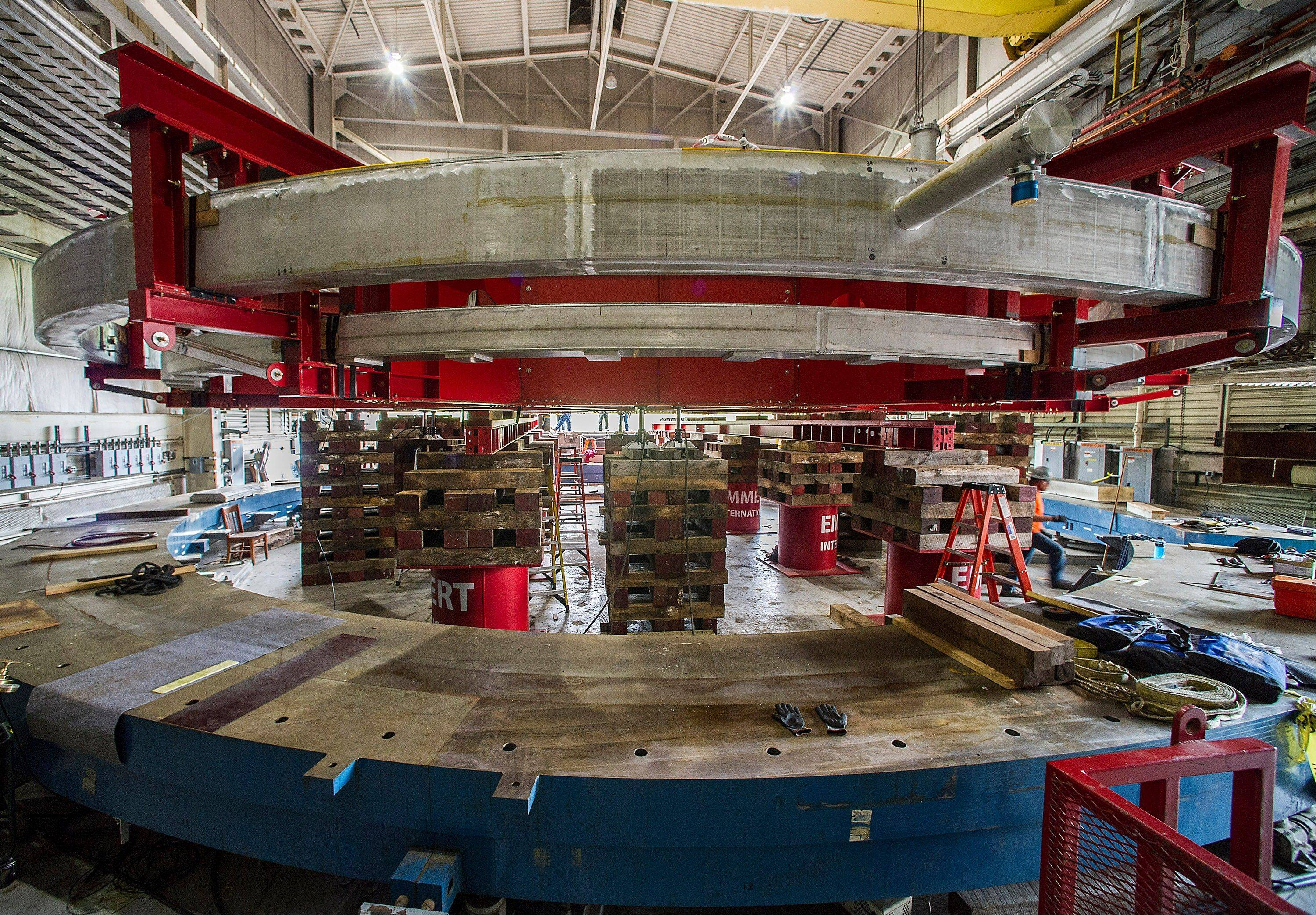 A red stabilizing apparatus carrying a 50-foot-wide electromagnet storage ring is seen at Brookhaven National Laboratory in Upton, N.Y., on eastern Long Island. The ring, which will capture subatomic particles that live only 2.2 millionths of a second, will be transported in one piece, and moved flat, to its new home at the U.S. Department of Energy's Fermi National Accelerator Laboratory in Batavia.