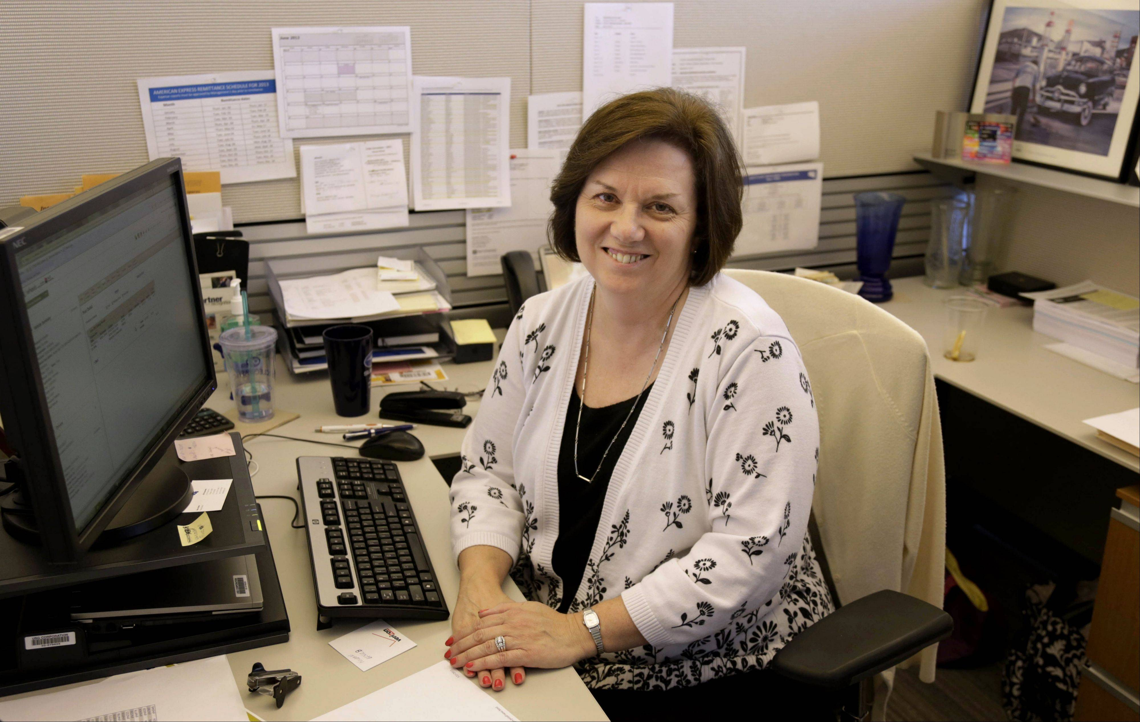 In this June 3, 2013, photo, Nora Kouba, an employee at USG Corporation sits at her workstation in Chicago. Over the years, Kouba has made use of a benefit offered by USG that allows their workers to buy and sell vacation time, a perk that gives workers more flexibility in managing their time off.