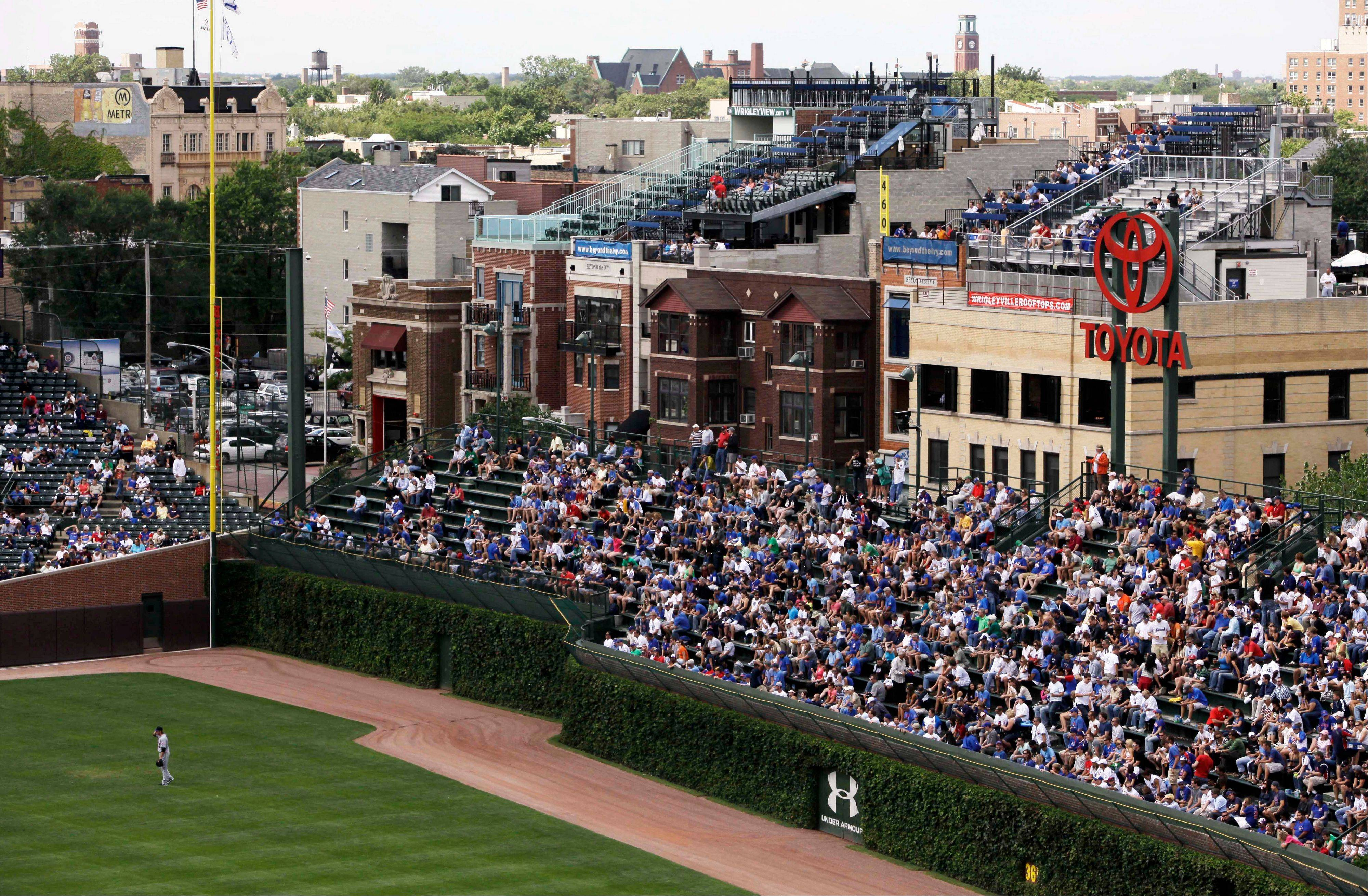 In this Sept. 3, 2010 file photo, spectators enjoy the view from one of the many rooftop bleachers along Waveland Avenue outside the left field wall at Wrigley Field during a Chicago Cubs baseball game in Chicago. A battle is heating up between the Cubs and rooftop owners as the team proposes renovations, including a Jumbotron in the bleachers, that would block the views and threaten the business those views have created. (AP Photo/Kiichiro Sato, File)