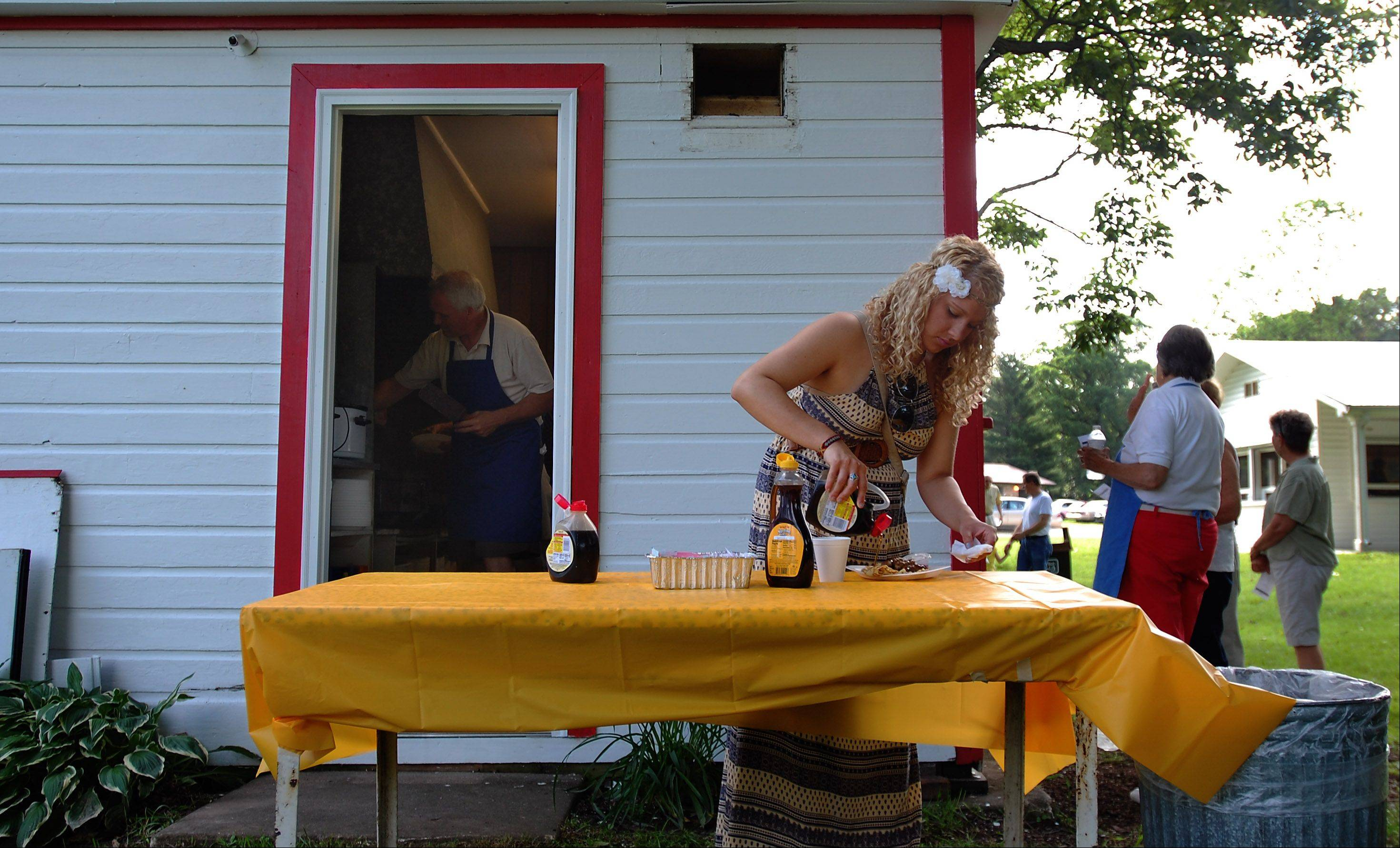Abra Keup adds syrup to her Swedish pancakes with lingonberries at the 103rd annual Swedish Midsommar Festival Sunday at Good Templar Park in Geneva. Abra attended with her dad for Father�s Day.