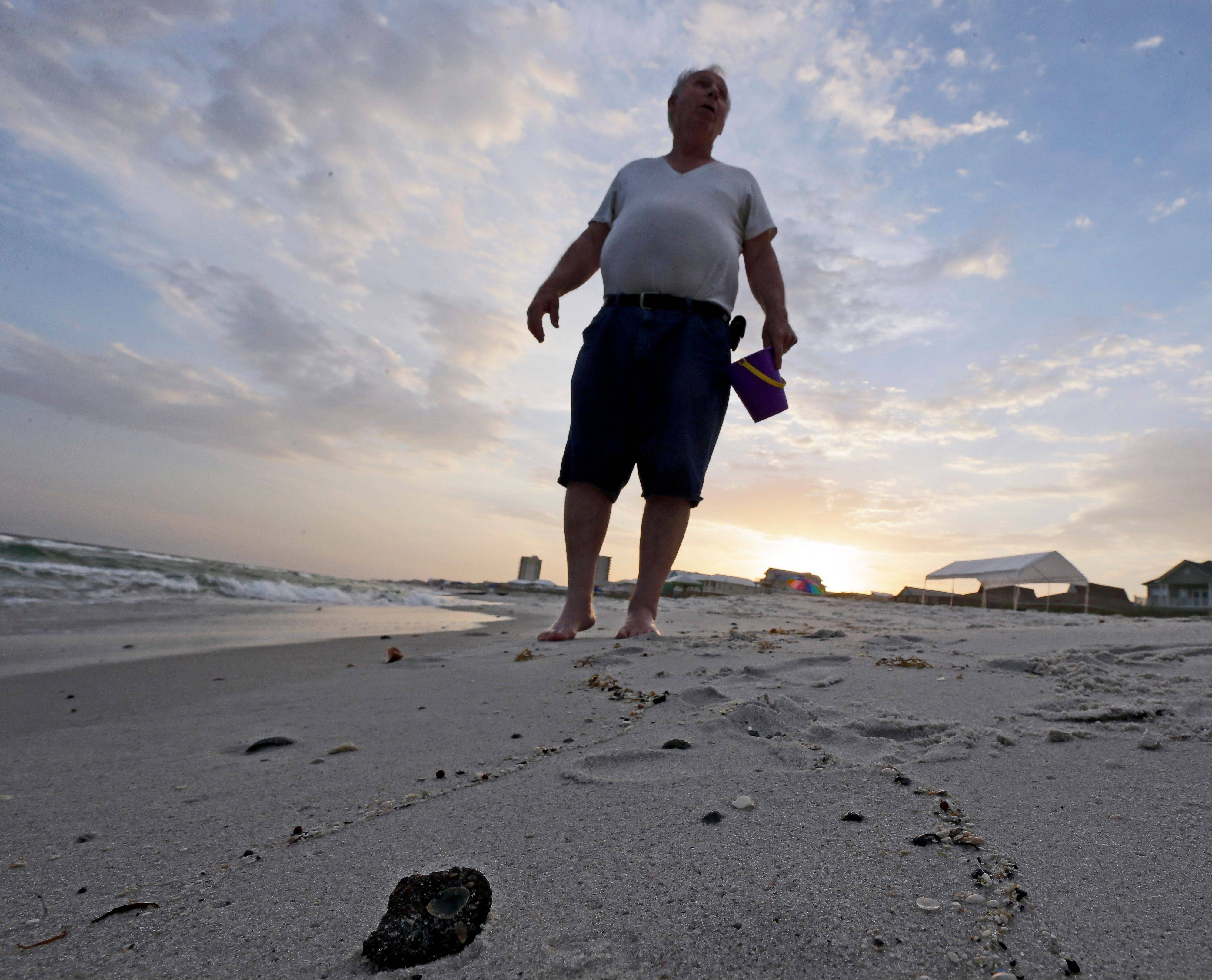 A small shell is embedded in a tar ball on the beach in Gulf Shores, Ala. After three years and $14 billion worth of work following the BP oil spill in the Gulf of Mexico, the petroleum giant and the Coast Guard say it's time to end extraordinary cleanup operations in Alabama, Florida and Mississippi.