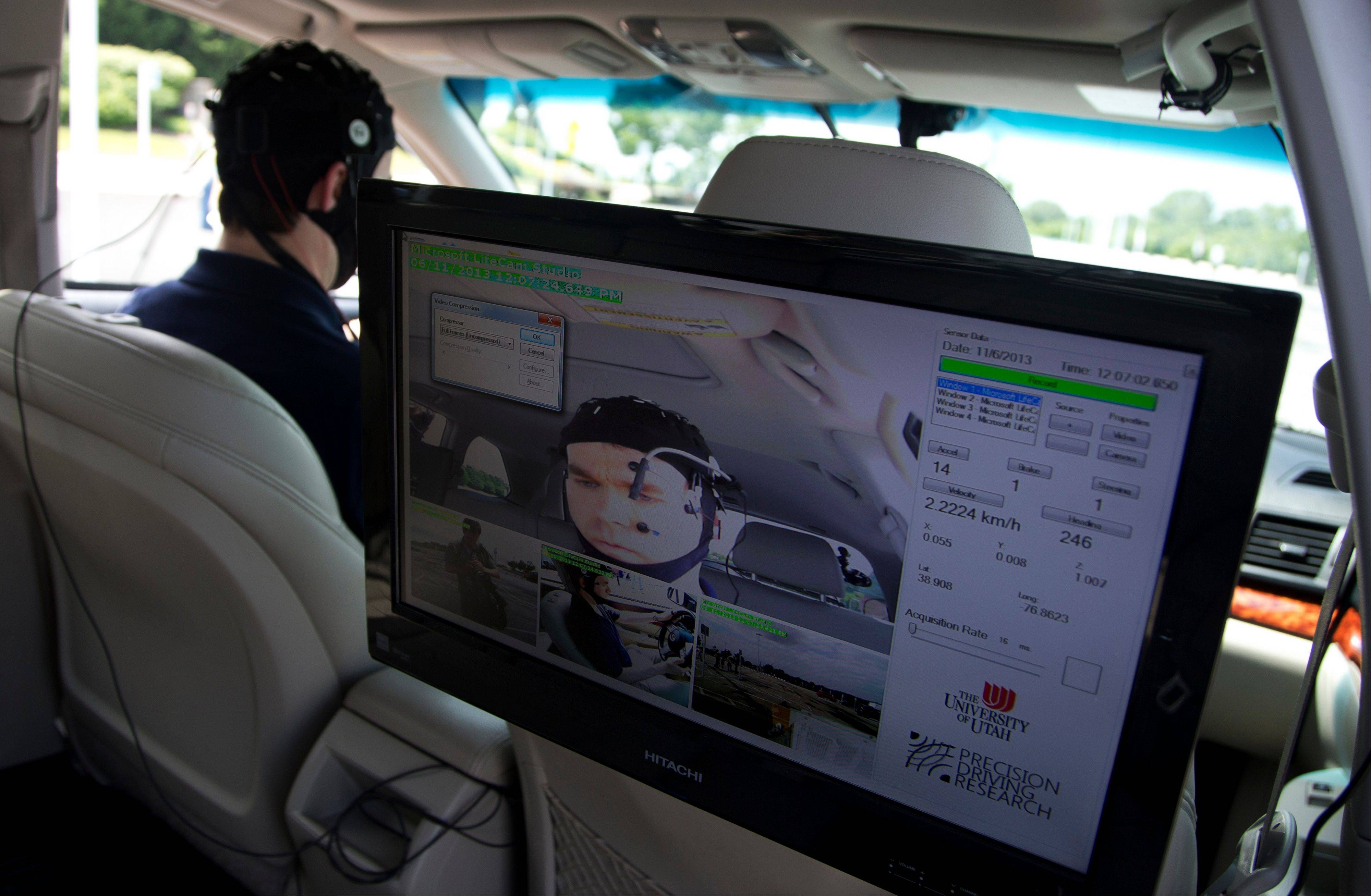 Russ Martin of American Automobile Association (AAA), is seen on a monitor in a research vehicle skull cap to the research vehicle during a demonstrations in support of their new study on distracted driving in Landover, Md.