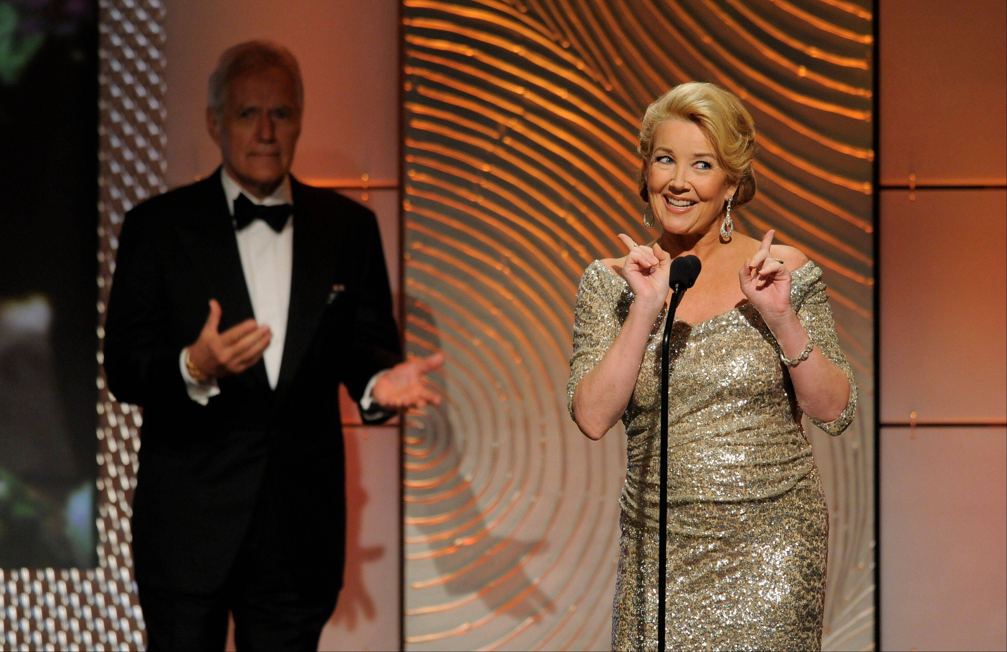 Melody Thomas Scott speaks on stage at the 40th Annual Daytime Emmy Awards on Sunday, June 16, 2013, in Beverly Hills, Calif. Looking on in background is Alex Trebek.