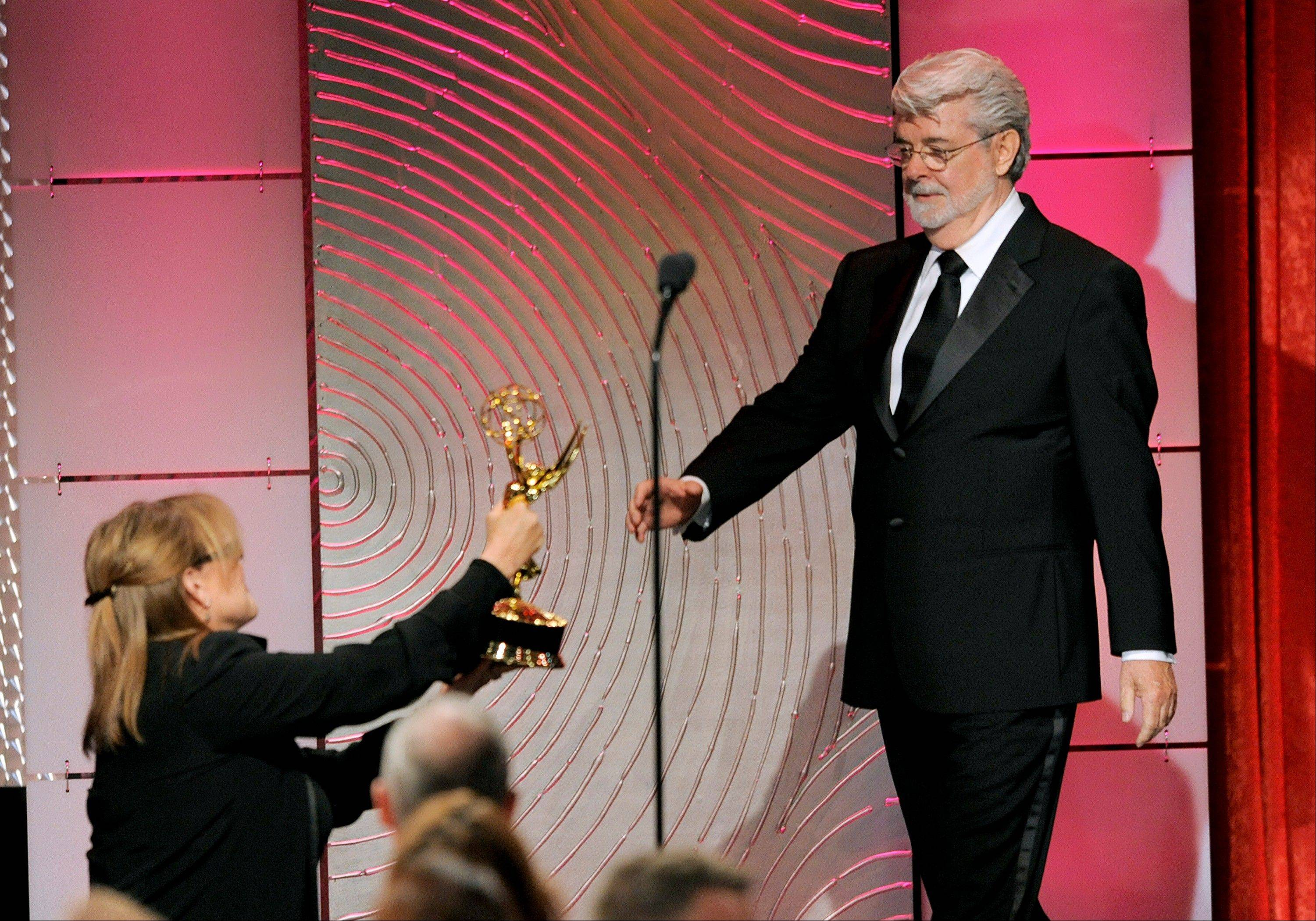 "Carrie Fisher, left, presents the award for outstanding special class animated program to George Lucas for ""Star Wars: The Clone Wars"" at the 40th Annual Daytime Emmy Awards on Sunday, June 16, 2013, in Beverly Hills, Calif."