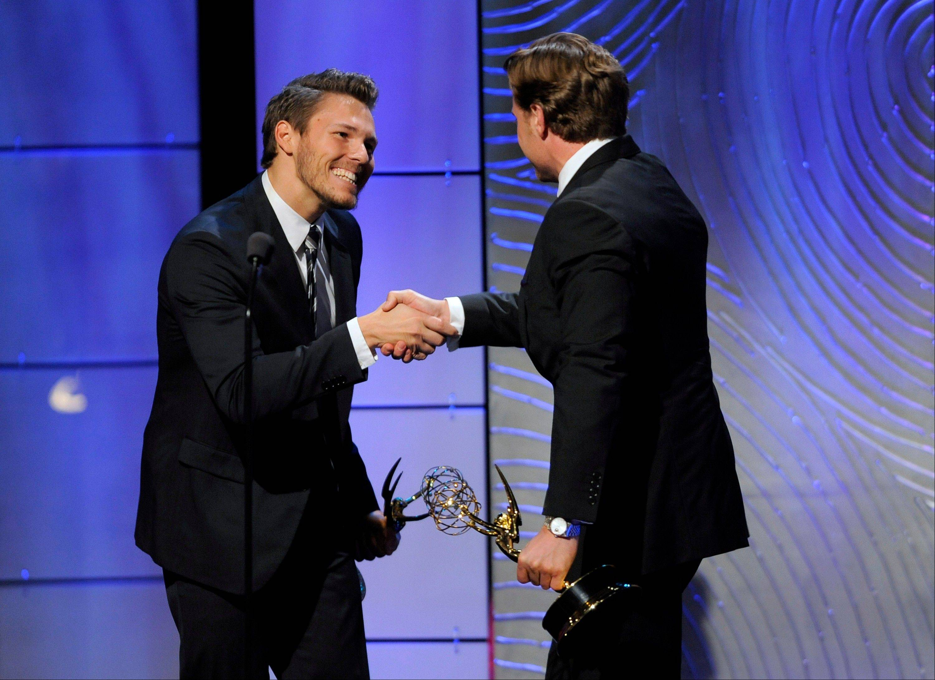 "Scott Clifton, left, from the cast of ""The Bold and the Beautiful,"" congratulates co-winner Billy Miller, from the cast of ""The Young and the Restless,"" as Miller accepts the award for outstanding supporting actor in a drama series at the 40th Annual Daytime Emmy Awards on Sunday, June 16, 2013, in Beverly Hills, Calif. In background is co-winner Scott Clifton."