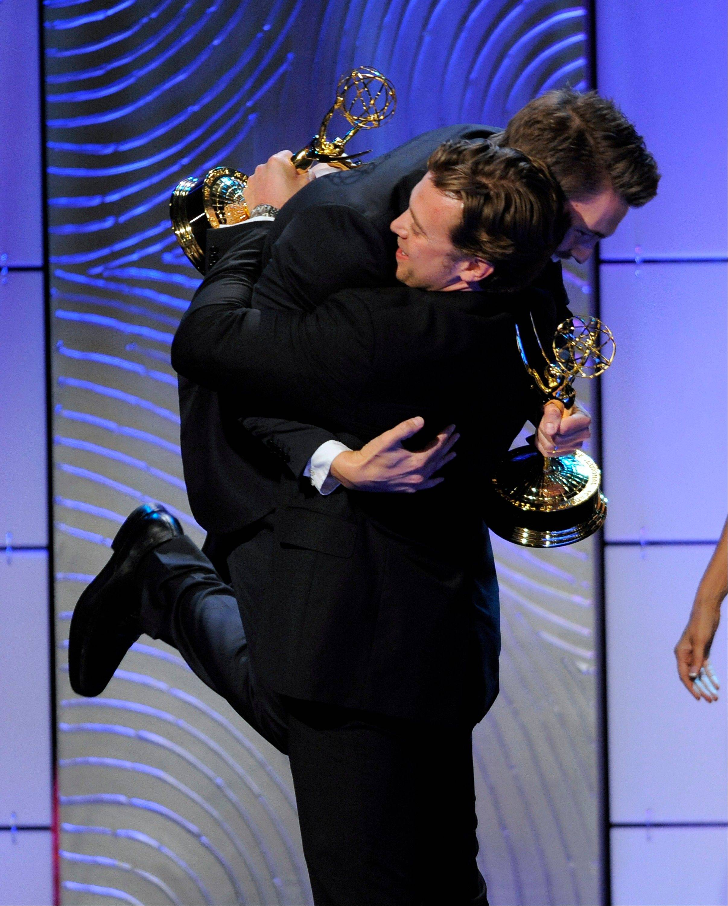 "Scott Clifton, left, from the cast of ""The Bold and the Beautiful,"" congratulates co-winner Billy Miller, from the cast of ""The Young and the Restless,"" as they accept the award for outstanding supporting actor in a drama series at the 40th Annual Daytime Emmy Awards on Sunday, June 16, 2013, in Beverly Hills, Calif. In background is co-winner Scott Clifton."