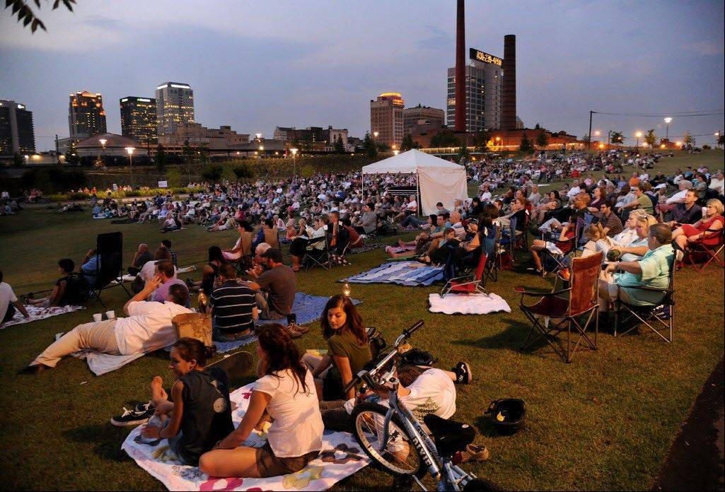 People sit on a hillside during a performance by the Alabama Symphony Orchestra in Railroad Park in Birmingham, Ala.
