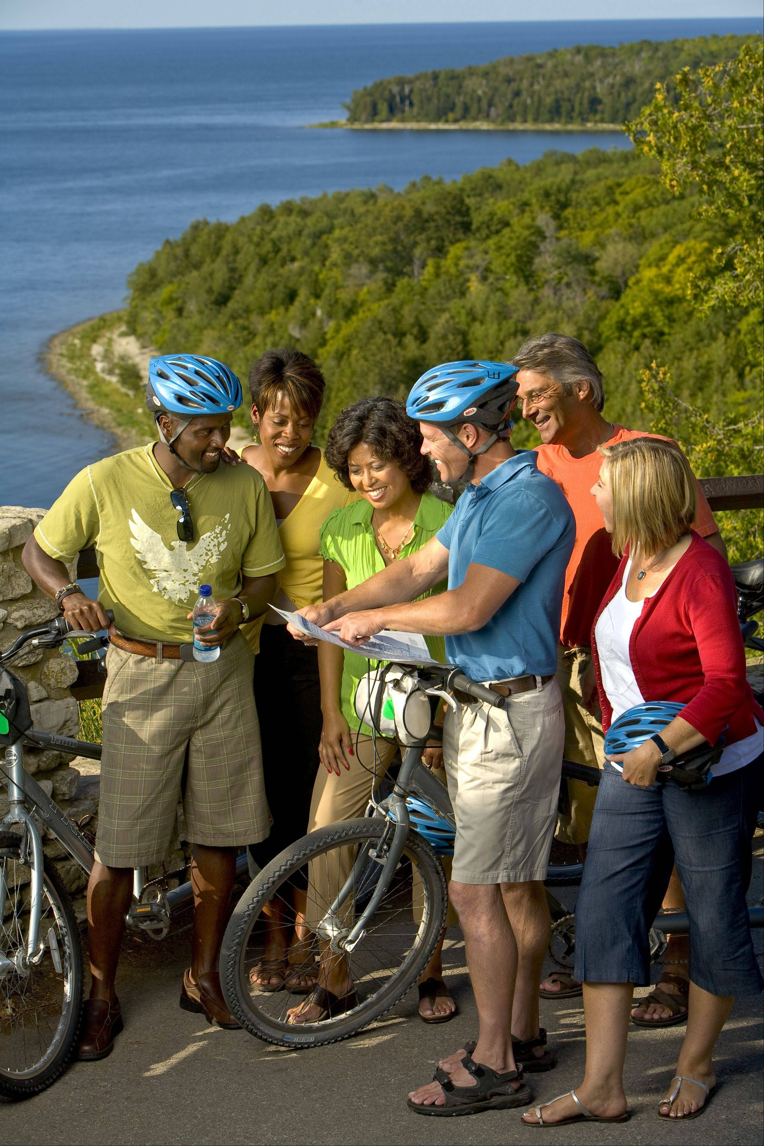 Bicyclists check out a bike map at scenic Sven's Bluff in Peninsula State Park along Door County's western coast.